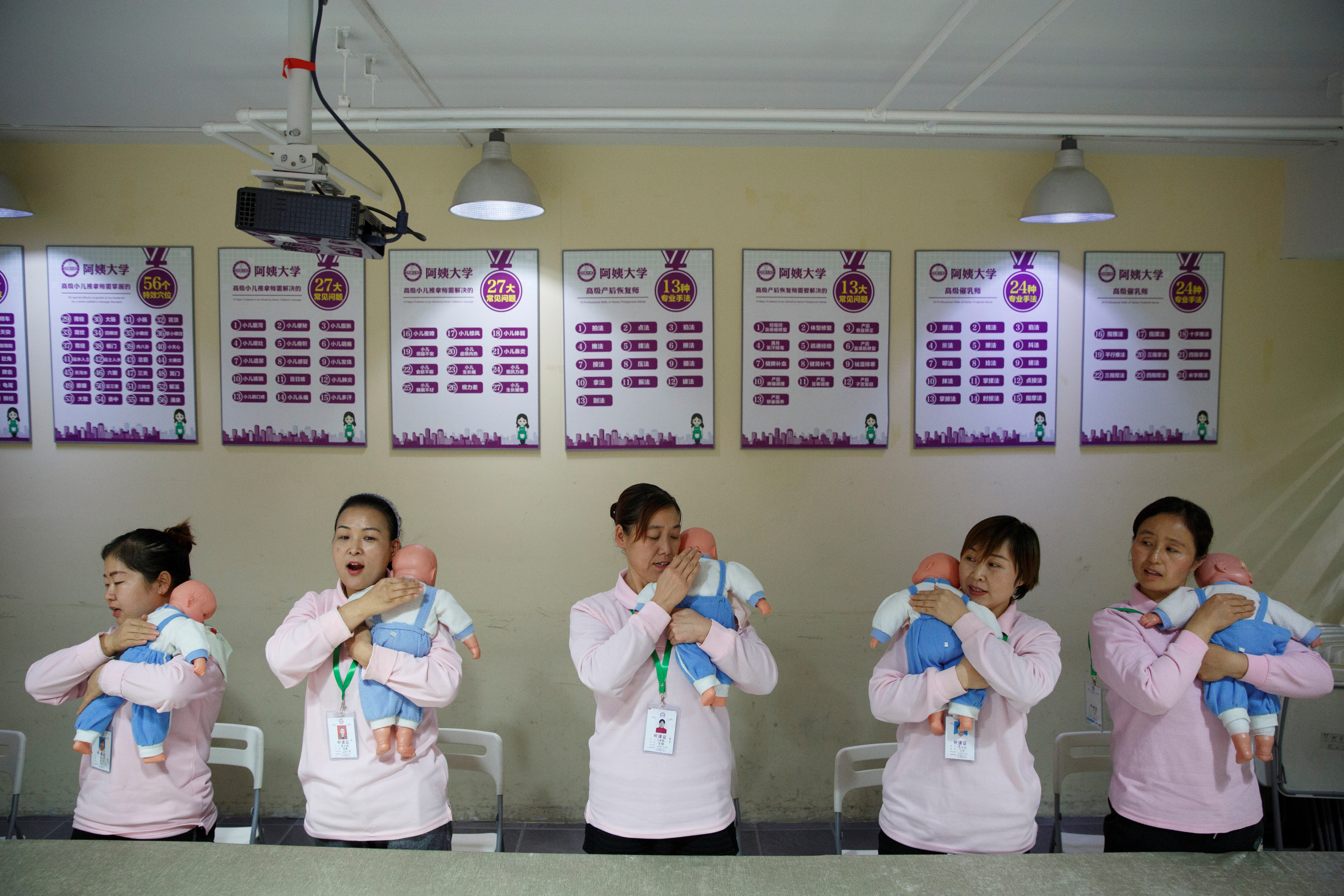 Students at Ayi University, a training program for domestic helpers, practice on baby dolls during a course teaching childcare in Beijing, China December 5, 2018.  REUTERS/Thomas Peter