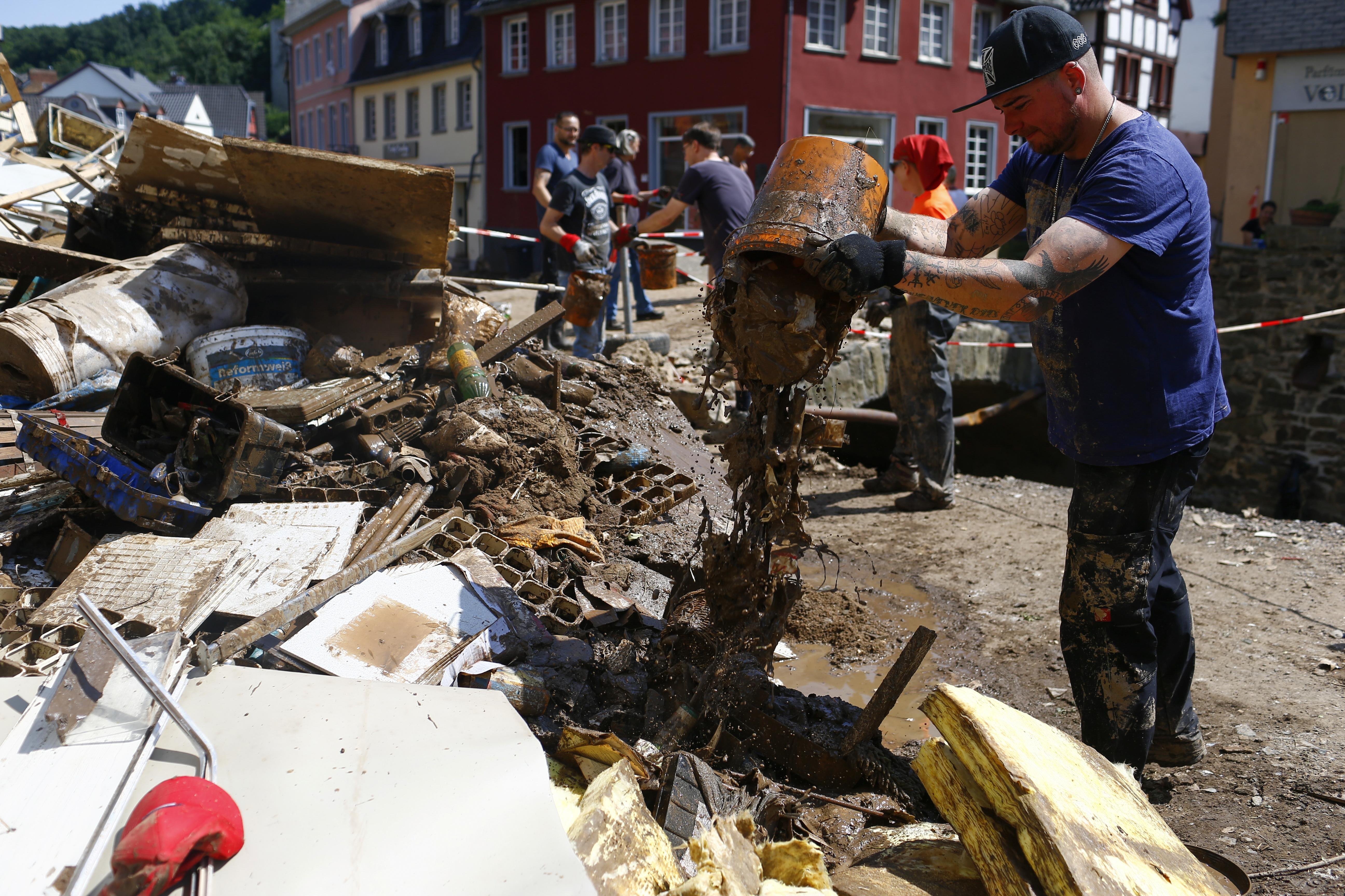 People help to clean up following heavy rainfalls, in Bad Muenstereifel, North Rhine-Westphalia state, Germany, July 21, 2021. REUTERS/Thilo Schmuelgen/File Photo