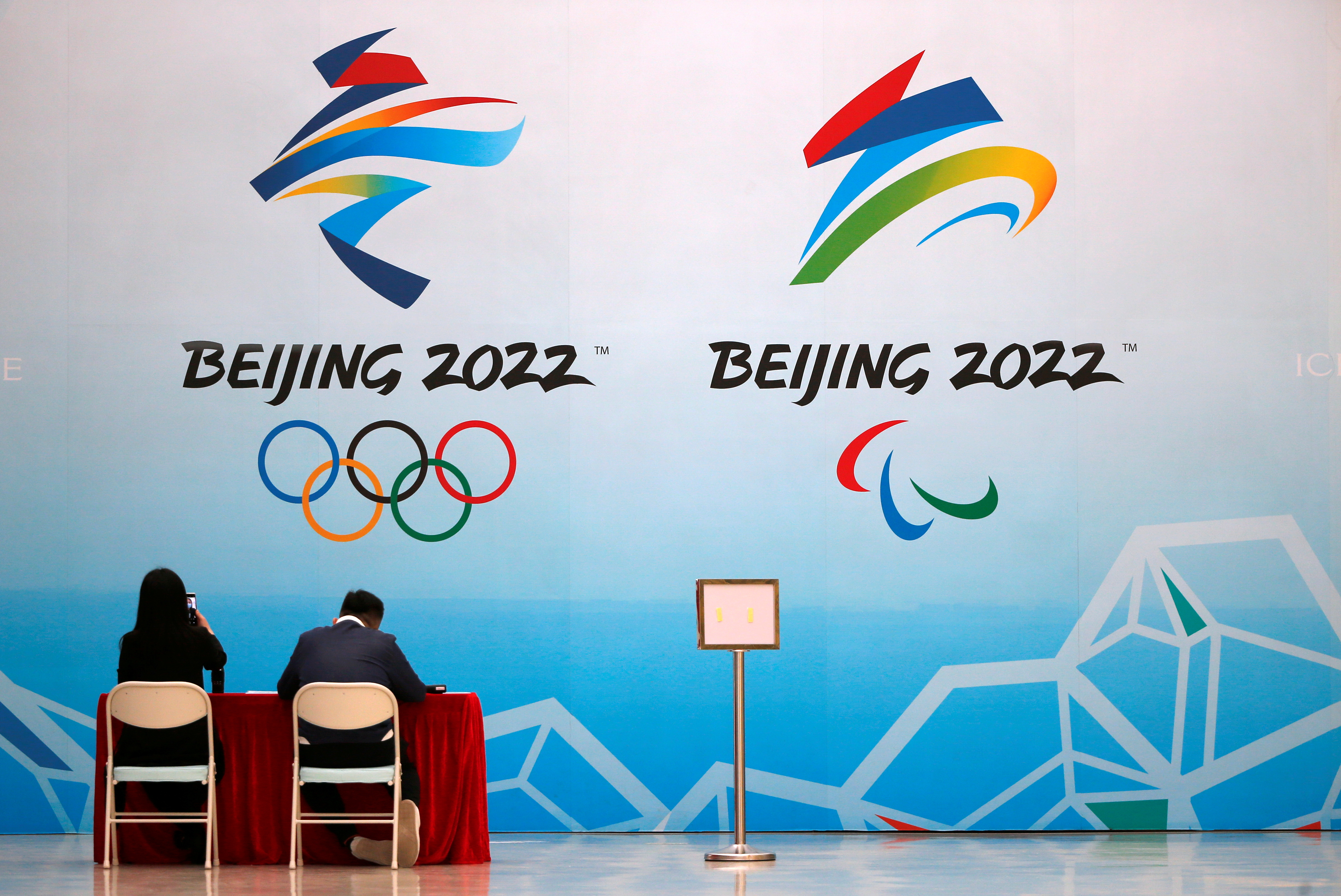 Staff members sit near a board with signs of the 2022 Olympic Winter Games, at the National Aquatics Center, known colloquially as the