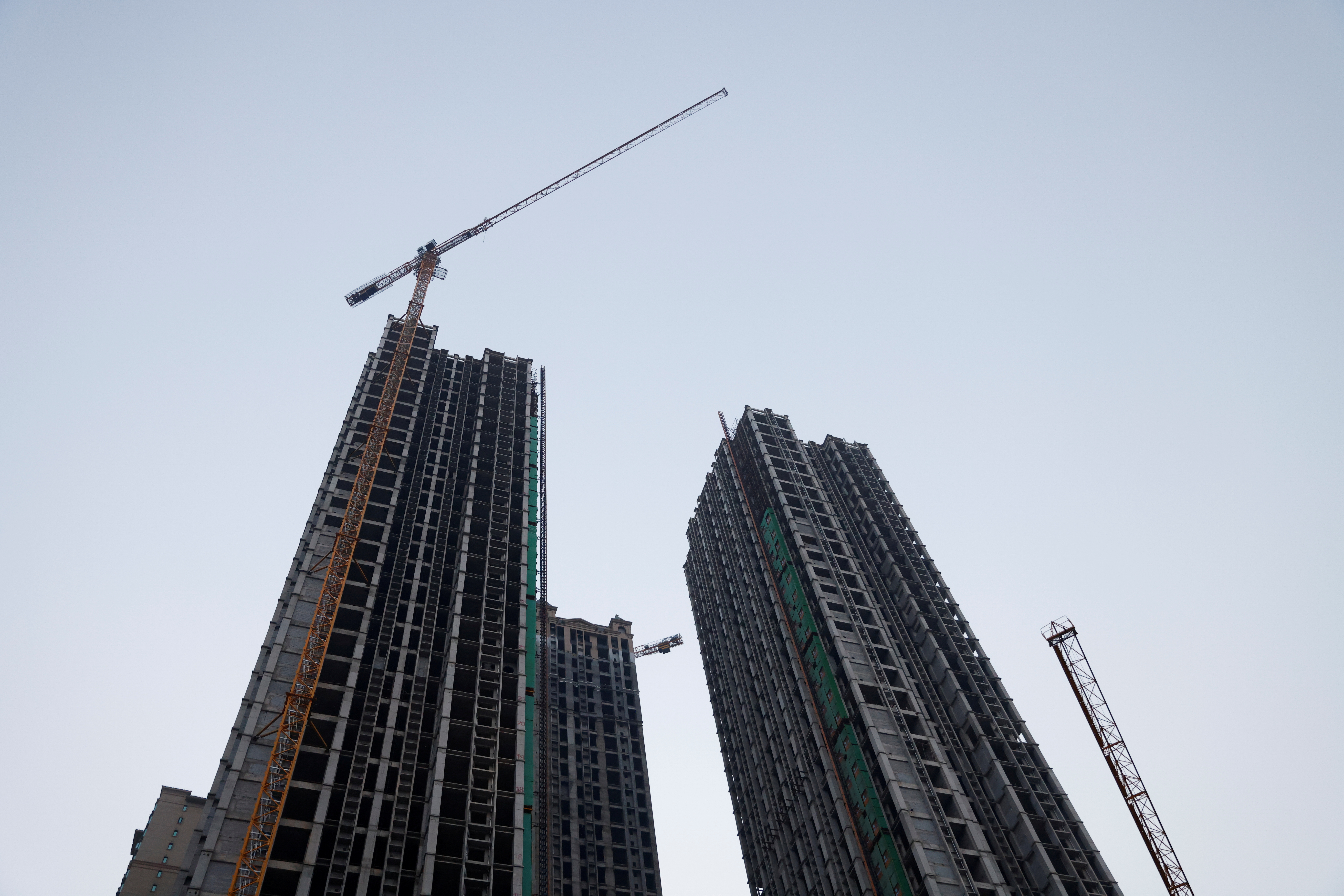 Cranes stand next to unfinished residential buildings at the Evergrande Oasis, a housing complex developed by Evergrande Group, in Luoyang, China September 15, 2021.  REUTERS/Carlos Garcia Rawlins/File Photo
