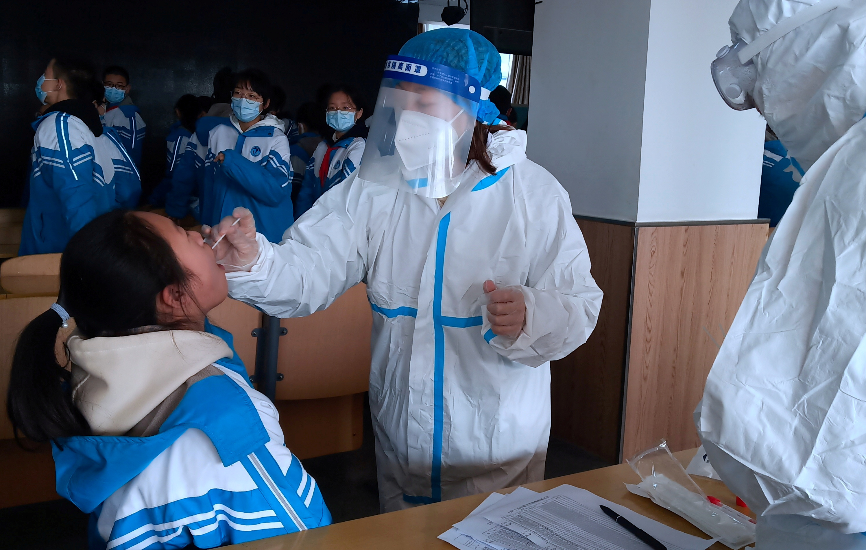 A medical worker in a protective suit collects a swab sample from a middle school student during a mass nucleic acid testing following a recent coronavirus disease (COVID-19) outbreak in Xingtai, Hebei province, China January 6, 2021. China Daily via REUTERS/File Photo