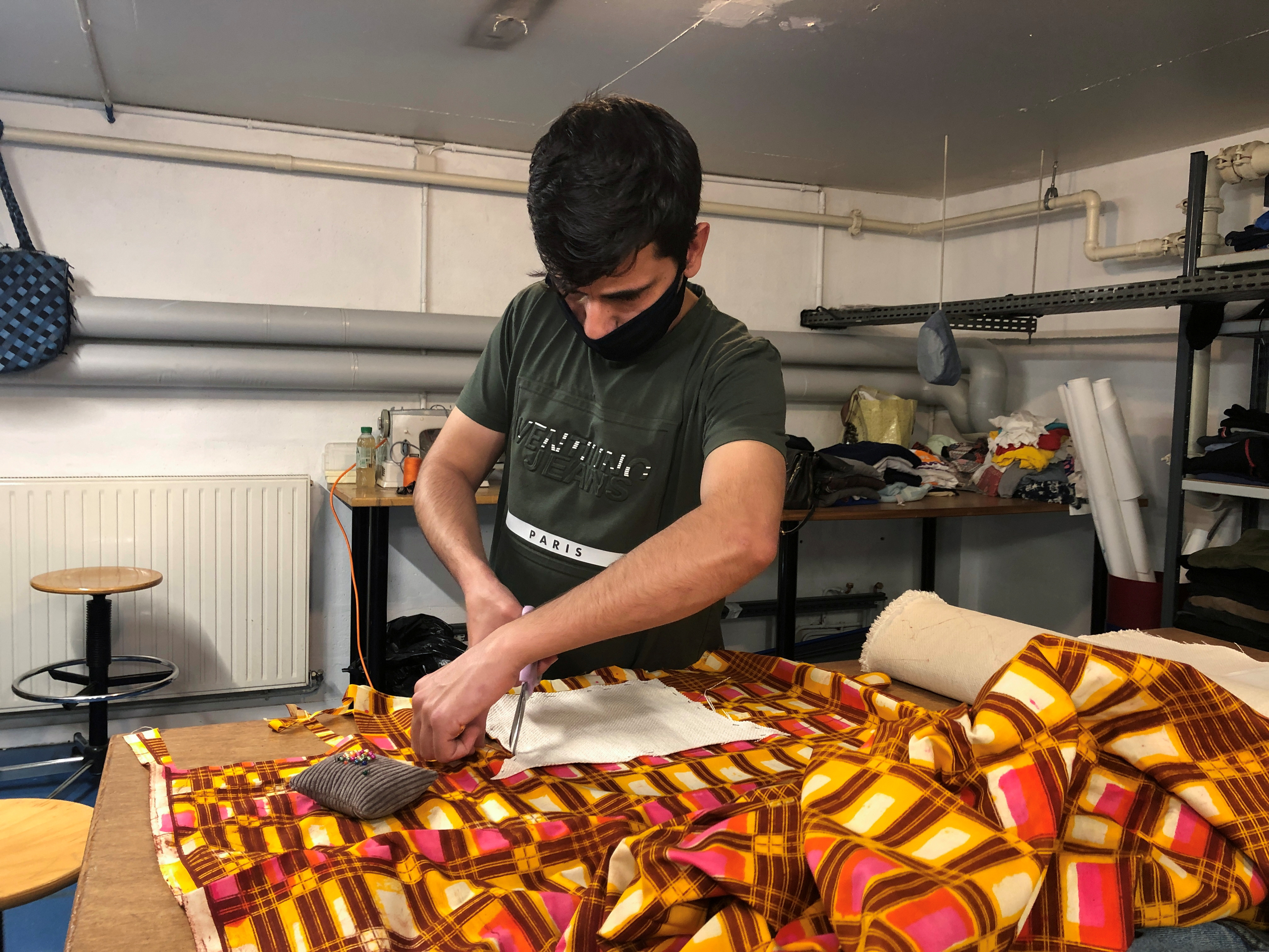 Afghan asylum seeker Haroon Sherzad cuts fabrics at a workshop in Antony, near Paris, France, June 11, 2021. Picture taken June 11, 2021. REUTERS/Michaela Cabrera