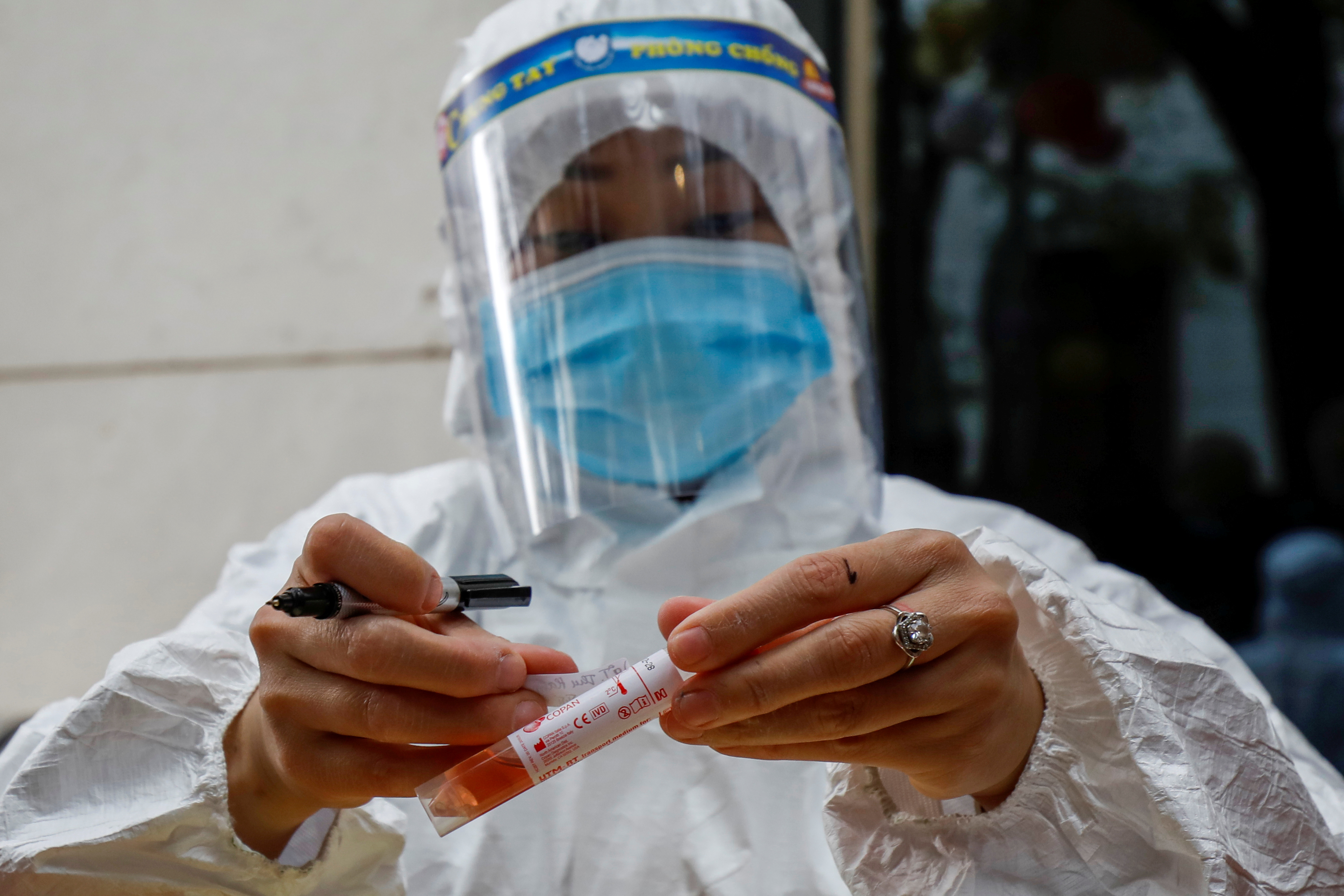 A health worker wearing a protective suit labels a sample tube at the National Convention Center, the venue for the 13th National Congress of the Communist Party of Vietnam, during the coronavirus disease (COVID-19) outbreak in Hanoi, Vietnam January 29, 2021. REUTERS/Kham