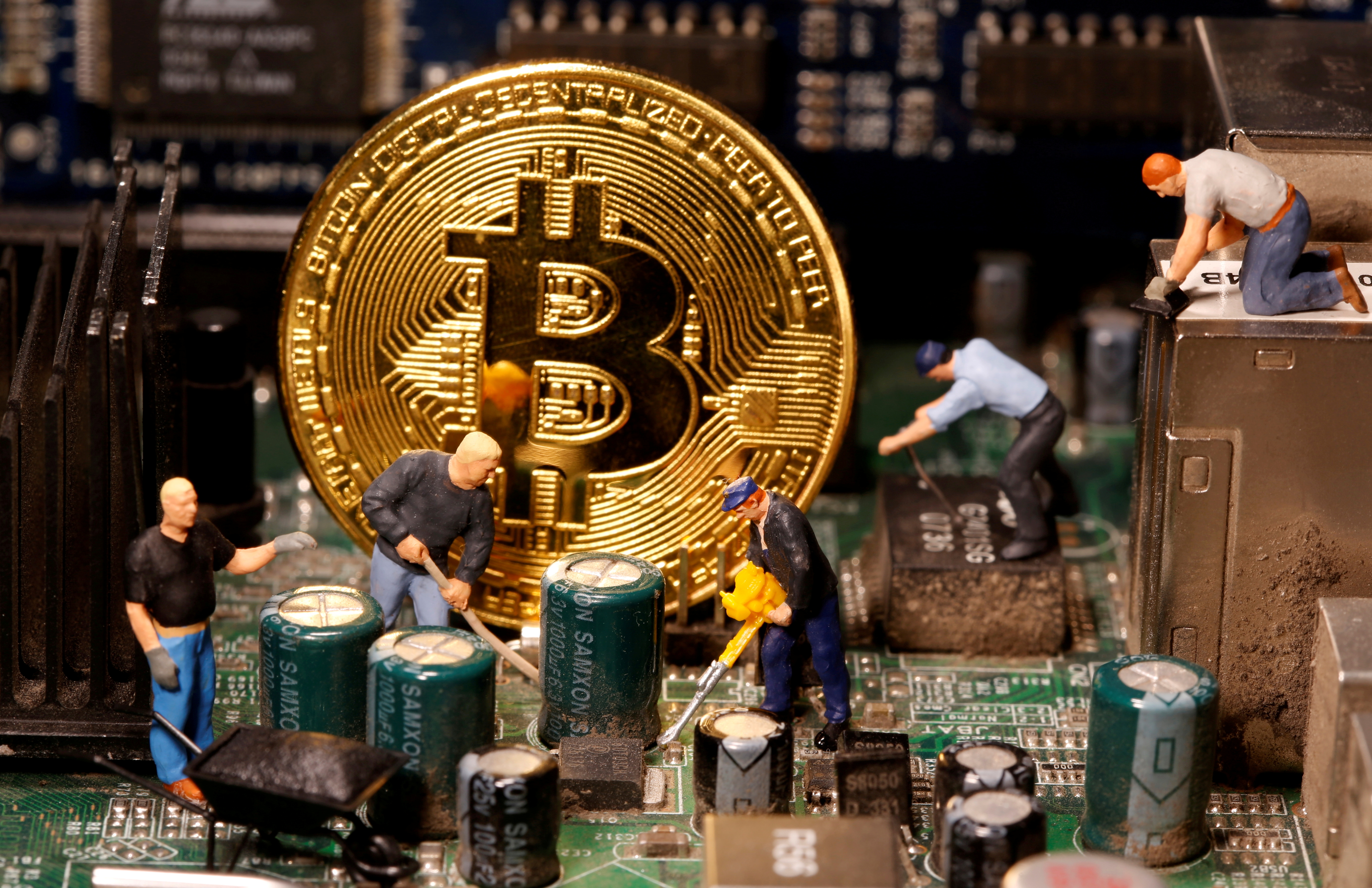 A representation of virtual currency Bitcoin and small toy figures are placed on computer motherboard in this illustration taken January 7, 2021. Picture is taken January 7, 2021. REUTERS/Dado Ruvic/File Photo