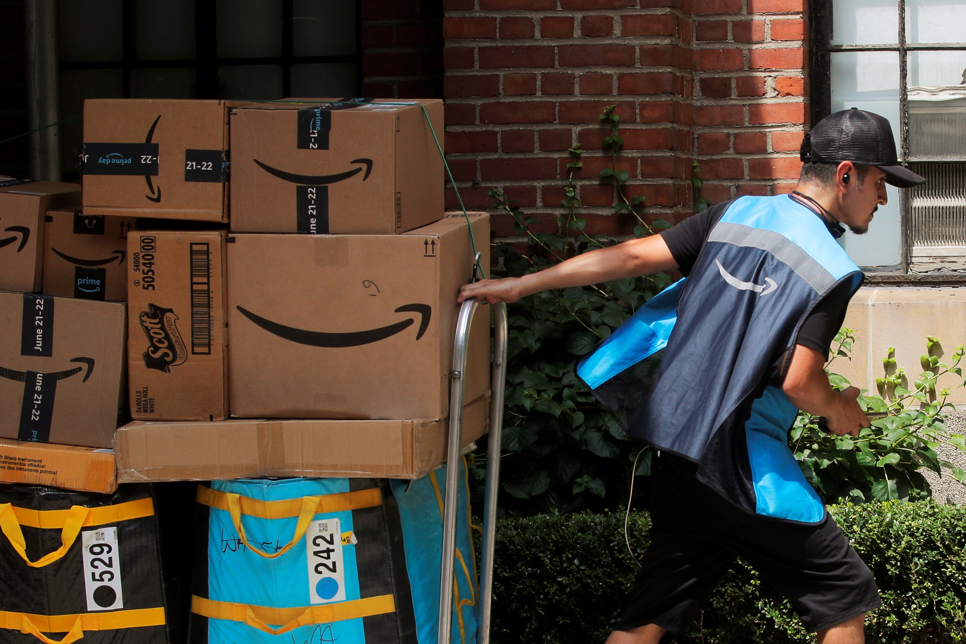 An Amazon delivery worker pulls a delivery cart full of packages during its annual Prime Day promotion in New York City, U.S., June 21, 2021.  REUTERS/Brendan McDermid