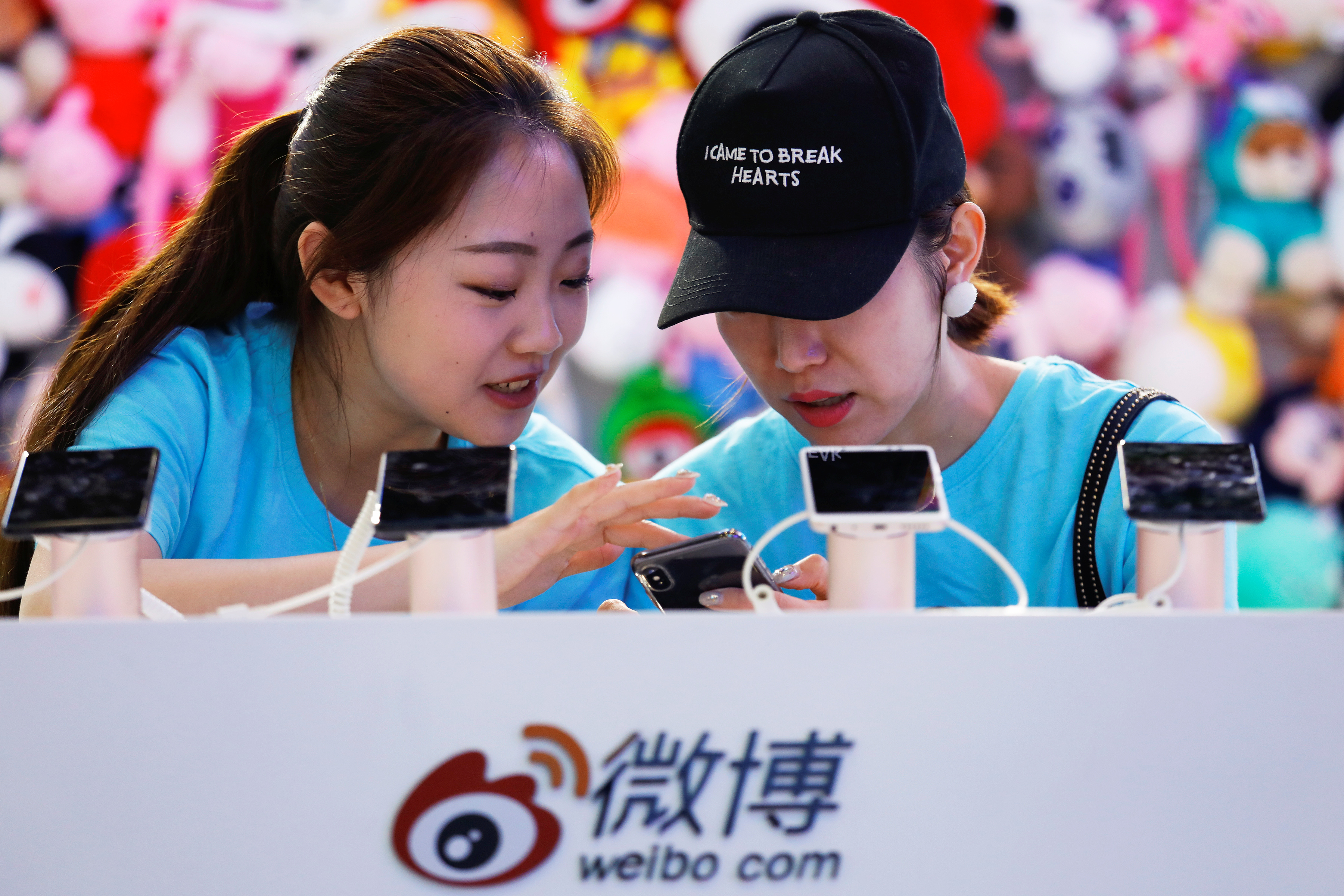 Members of staff use a smartphone at  Sina Weibo's booth during Global Mobile Internet Conference (GMIC) at the National Convention in Beijing, China April 27, 2018. REUTERS/Damir Sagolj - RC14E832BBF0