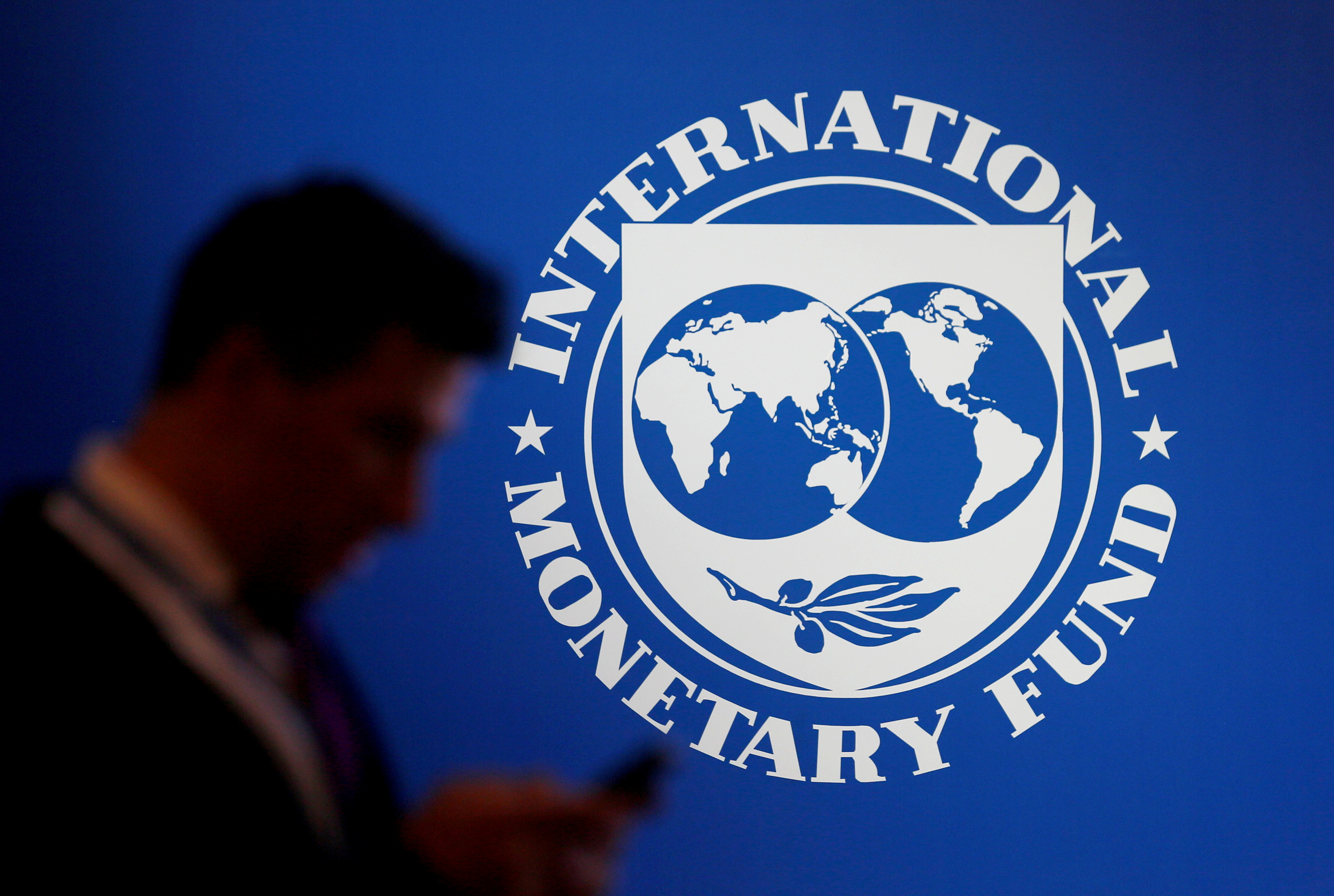 A participant stands near a logo of IMF at the International Monetary Fund - World Bank Annual Meeting 2018 in Nusa Dua, Bali, Indonesia, October 12, 2018. REUTERS/Johannes P. Christo/File Photo