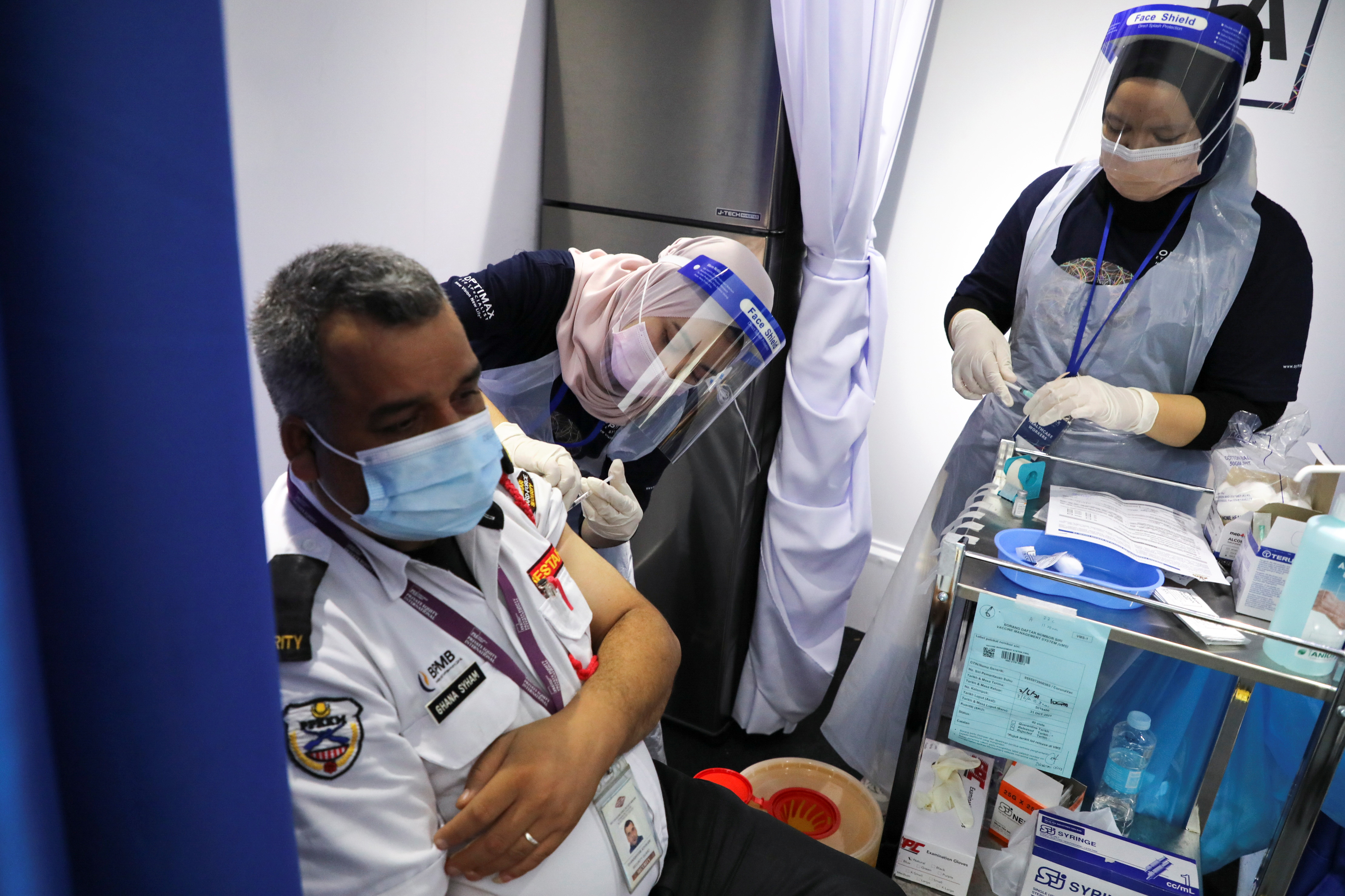 A foreign worker receives a dose of the Sinovac vaccine against the coronavirus disease (COVID-19), in a vaccination truck in Kuala Lumpur, Malaysia June 8, 2021. REUTERS/Lim Huey Teng