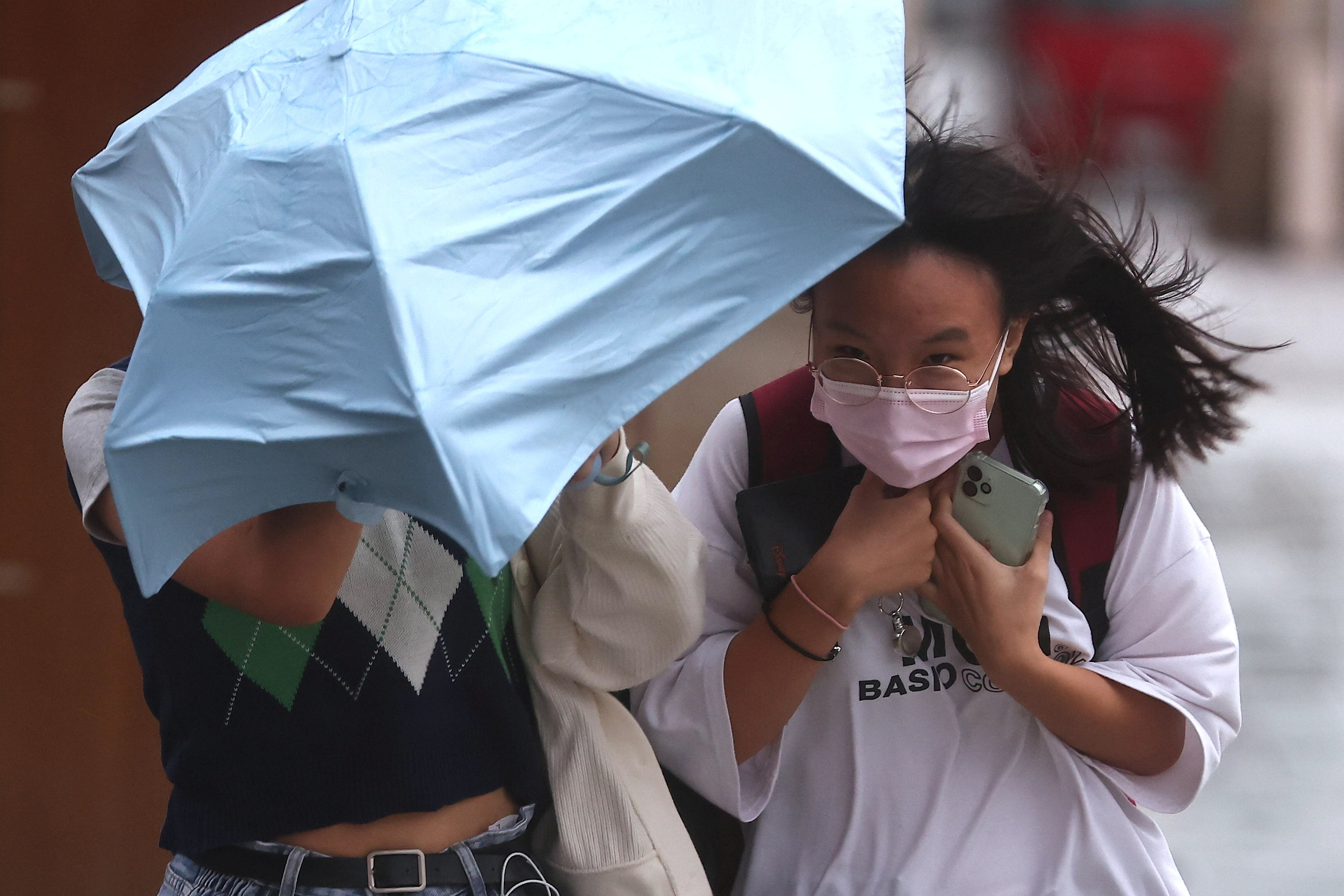 People walk in strong wind and rain caused by Typhoon Chanthu in Taipei, Taiwan, September 12, 2021. REUTERS/Ann Wang