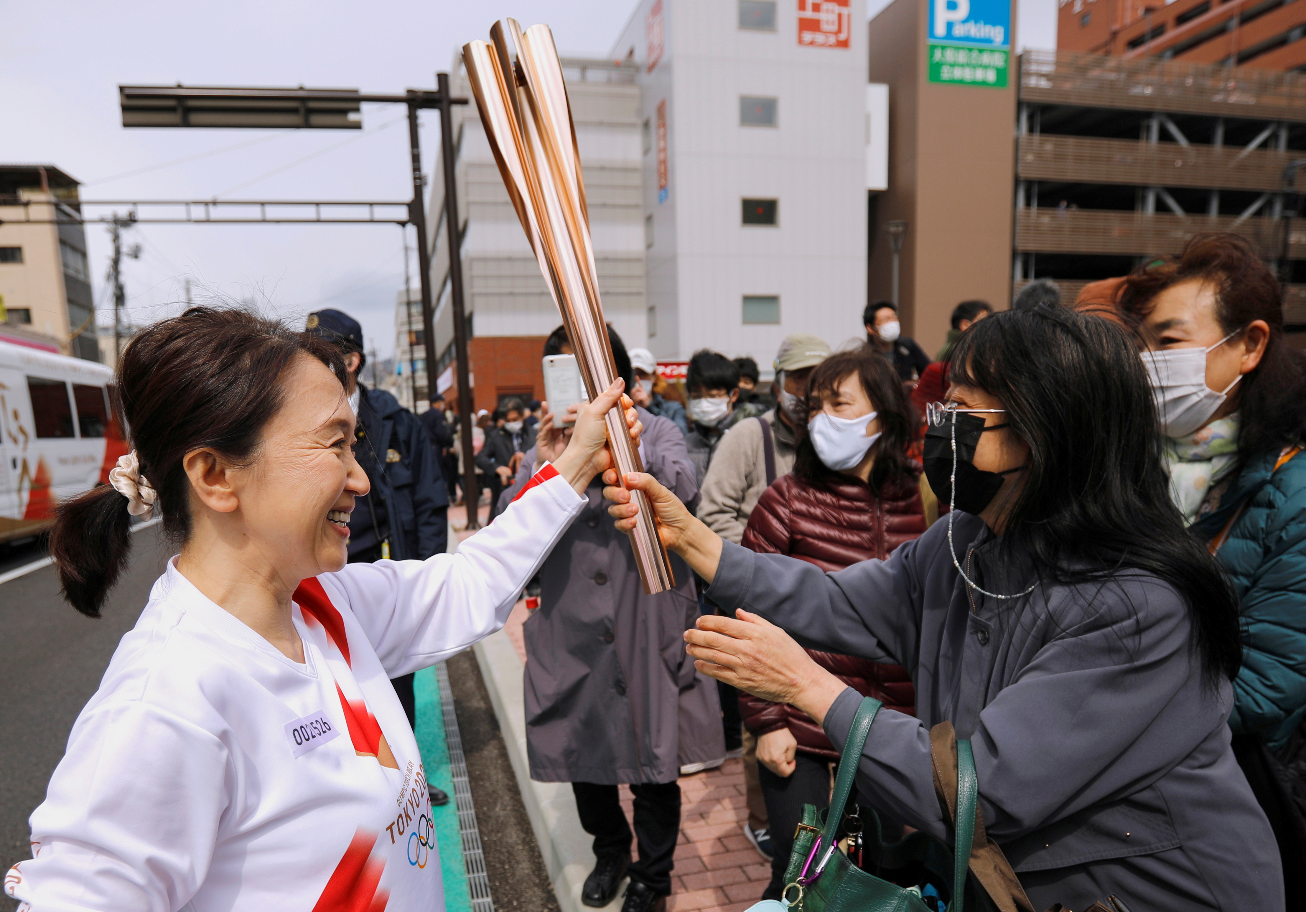 Spectators try to touch the torch carried by torchbearer Junko Ito, after her run during the Tokyo 2020 Olympic torch relay on the second day of the relay in Fukushima, Japan March 26, 2021. REUTERS/Issei Kato/File Photo