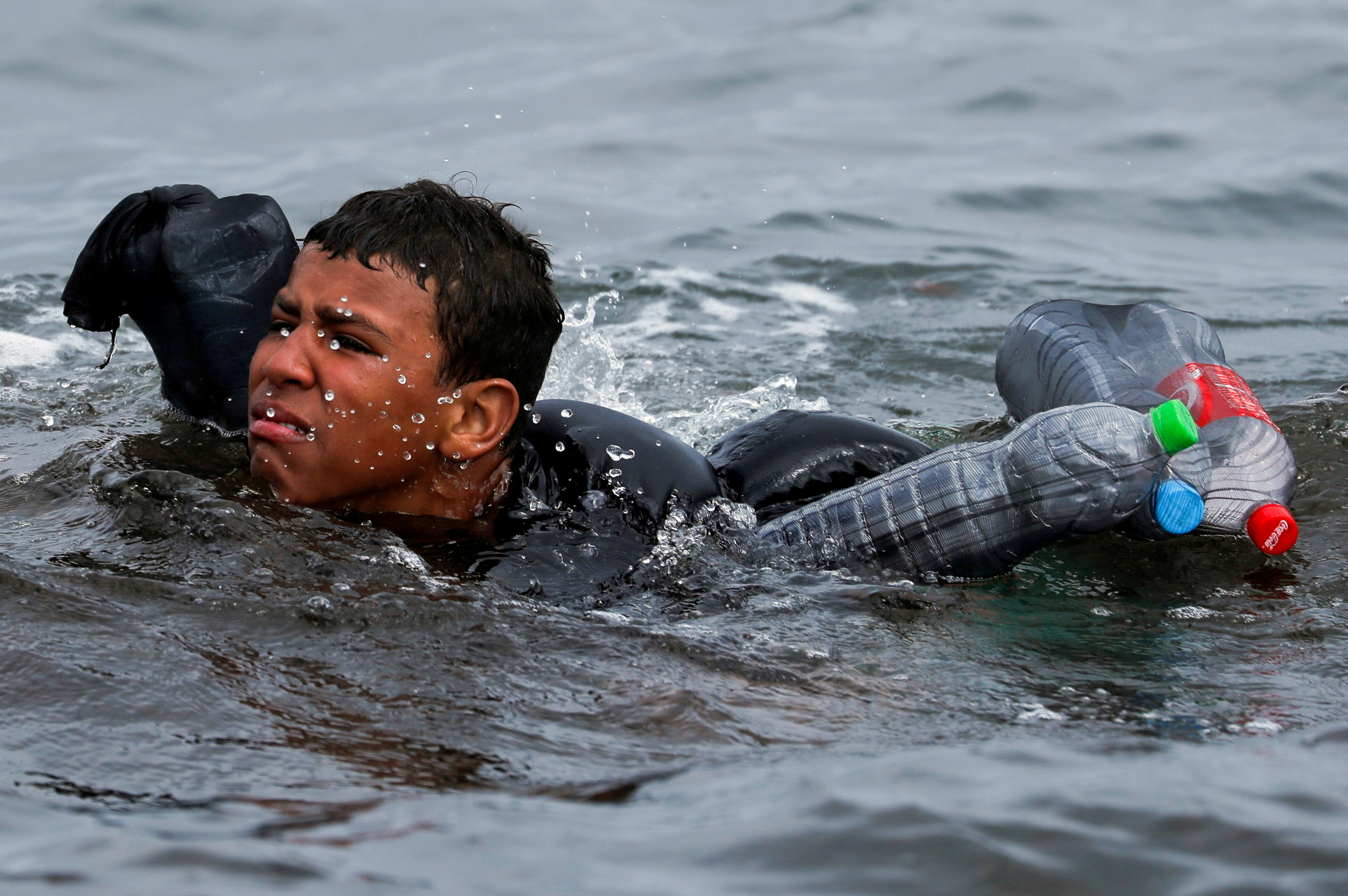A Moroccan boy swims using bottles as a float, near the fence between the Spanish-Moroccan border, after thousands of migrants swam across the border, in Ceuta, Spain, May 19, 2021. REUTERS/Jon Nazca