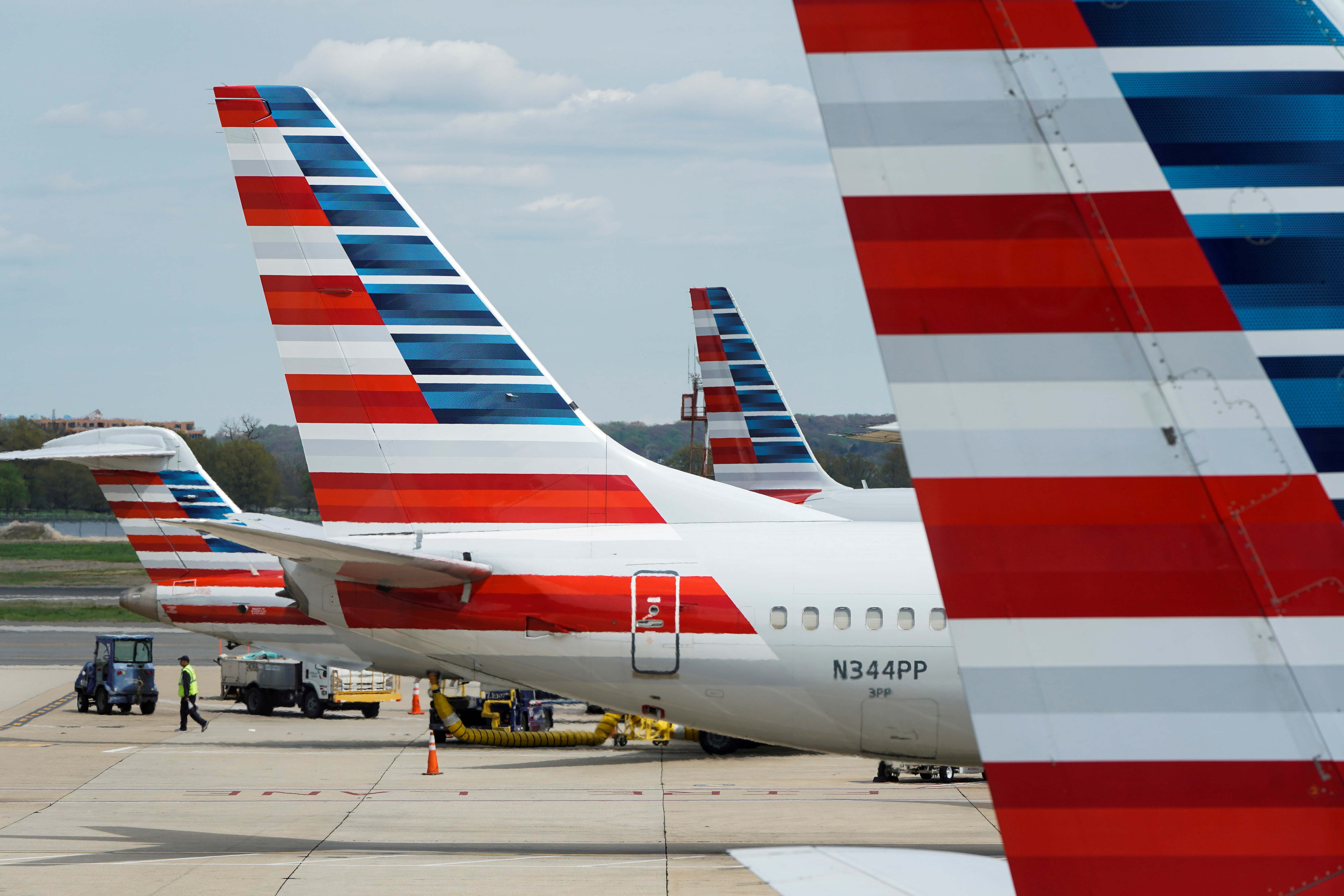 A member of a ground crew walks past American Airlines planes parked at the gate at Ronald Reagan National Airport in Washington, U.S., April 5, 2020.      REUTERS/Joshua Roberts/File Photo