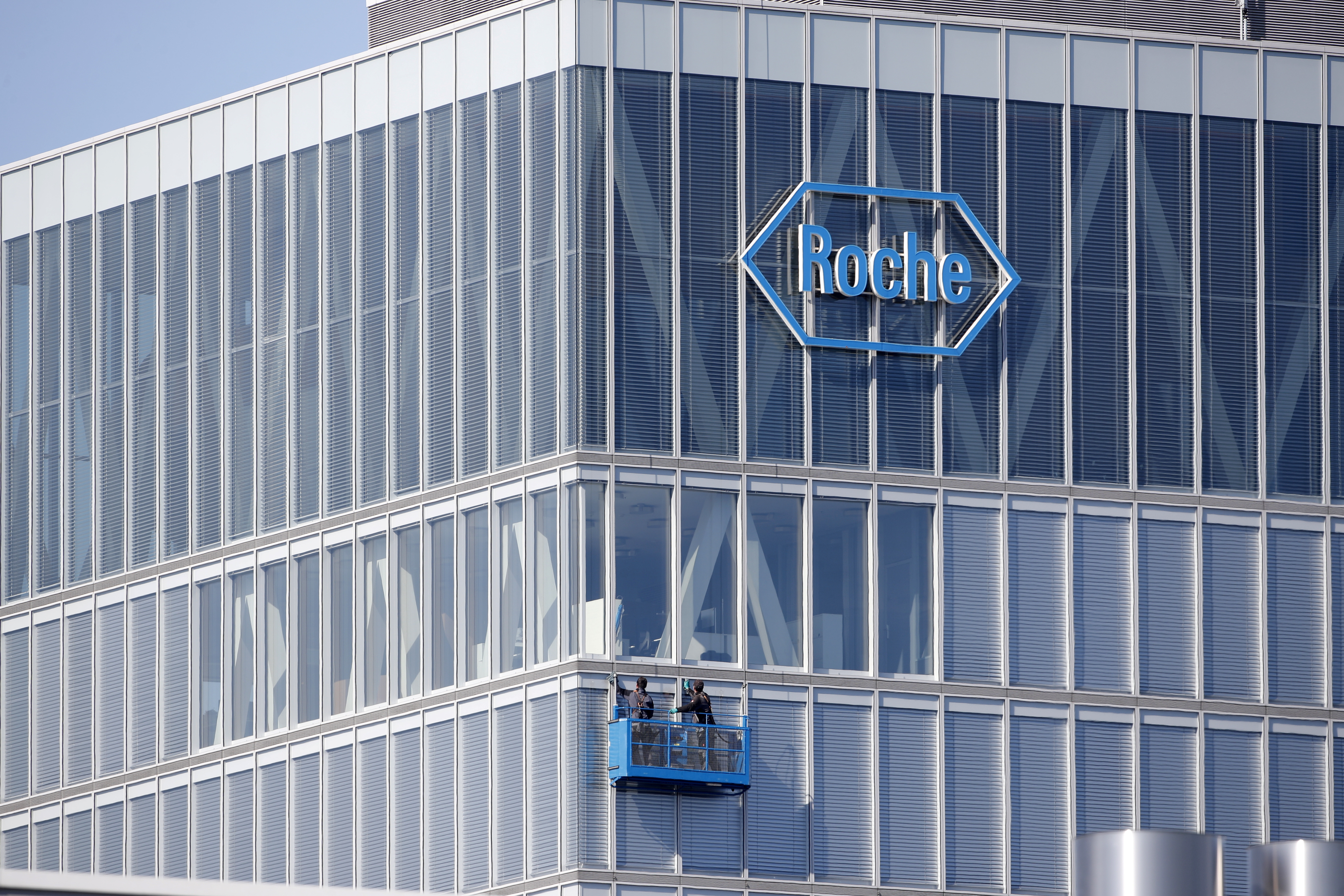 Workers clean the windows of a building of Roche in Rotkreuz May 27, 2020. REUTERS/Arnd Wiegmann/File Photo