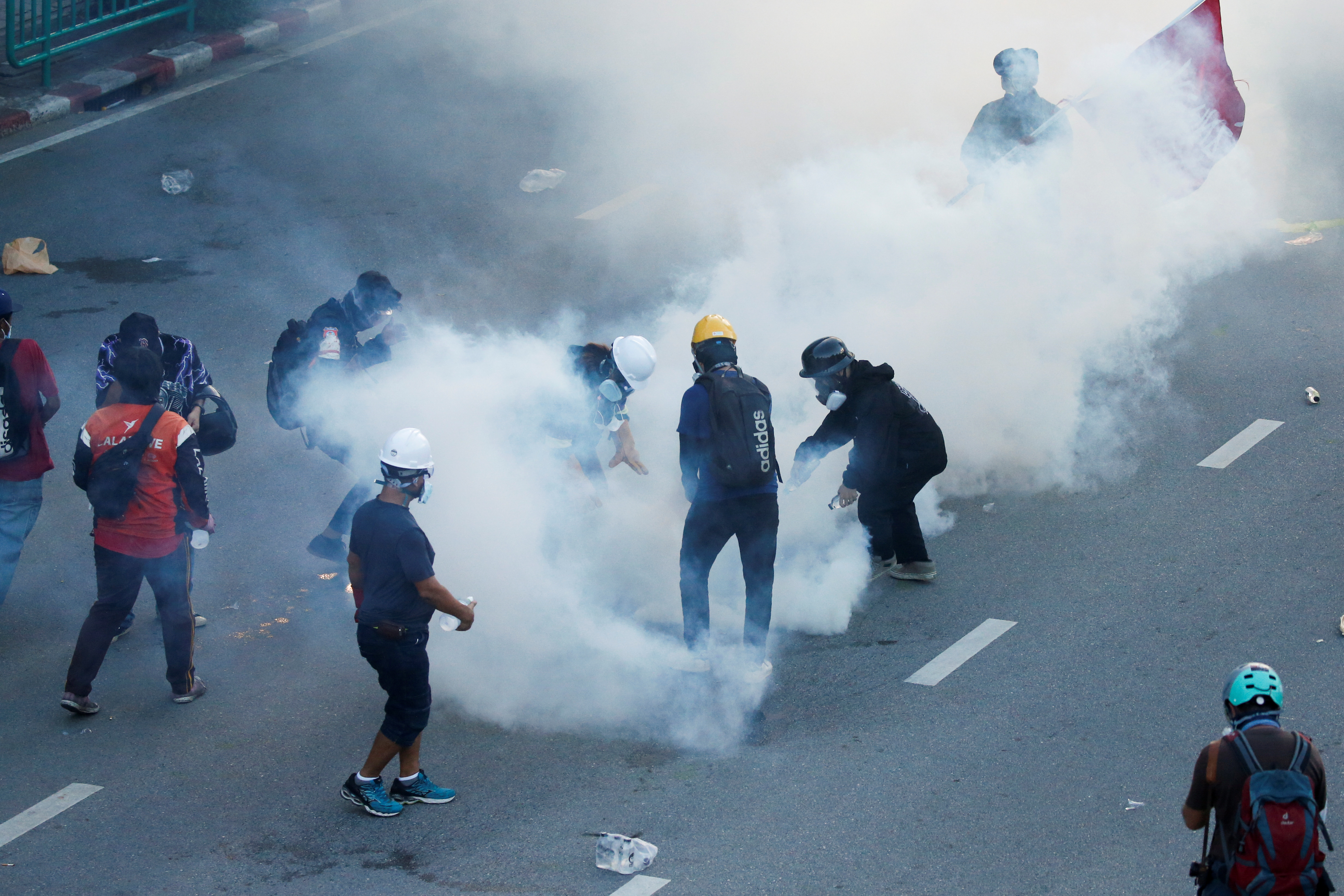 People stand among tear gas during a protest over the government's handling of the coronavirus disease (COVID-19) pandemic, in Bangkok, Thailand, August 16, 2021. REUTERS/Soe Zeya Tun