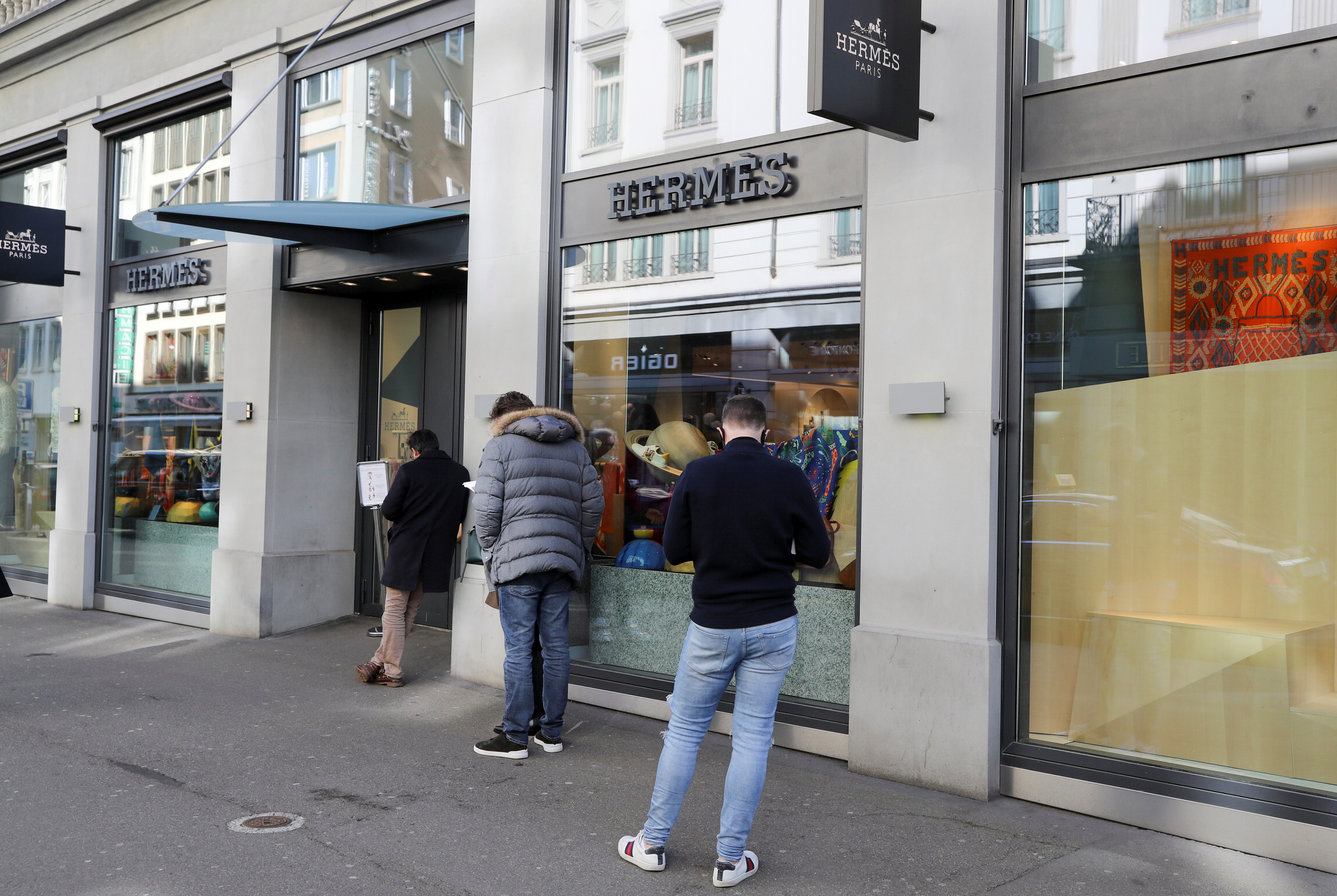 Shoppers queue in front of a re-opened store of French luxury house Hermes after the Swiss government relaxed some of its COVID-19 restrictions, as the spread of the coronavirus disease (COVID-19) continues, at the Bahnhofstrasse shopping street in Zurich, Switzerland March 1, 2021. REUTERS/Arnd Wiegmann/File photo