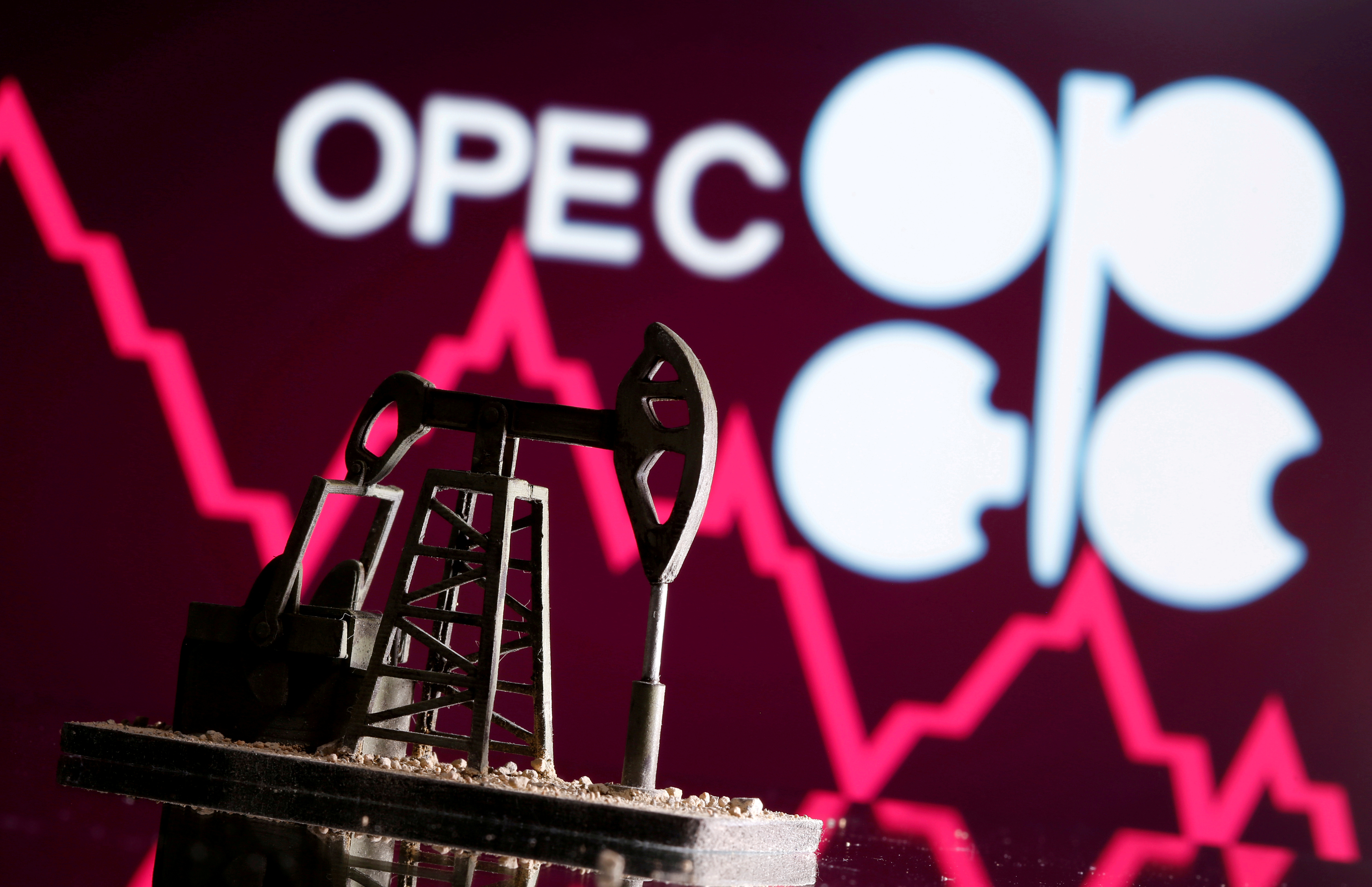 A 3D printed oil pump jack is seen in front of displayed stock graph and Opec logo in this illustration picture, April 14, 2020. REUTERS/Dado Ruvic/Illustration//File Photo