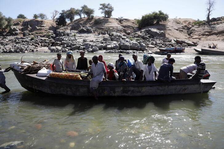 Ethiopians fleeing from the Tigray region arrive by boat to Sudan after crossing a river between the two countries, near the Hamdayet refugee transit camp, Sudan, December 1, 2020. REUTERS/Baz Ratner/File Photo