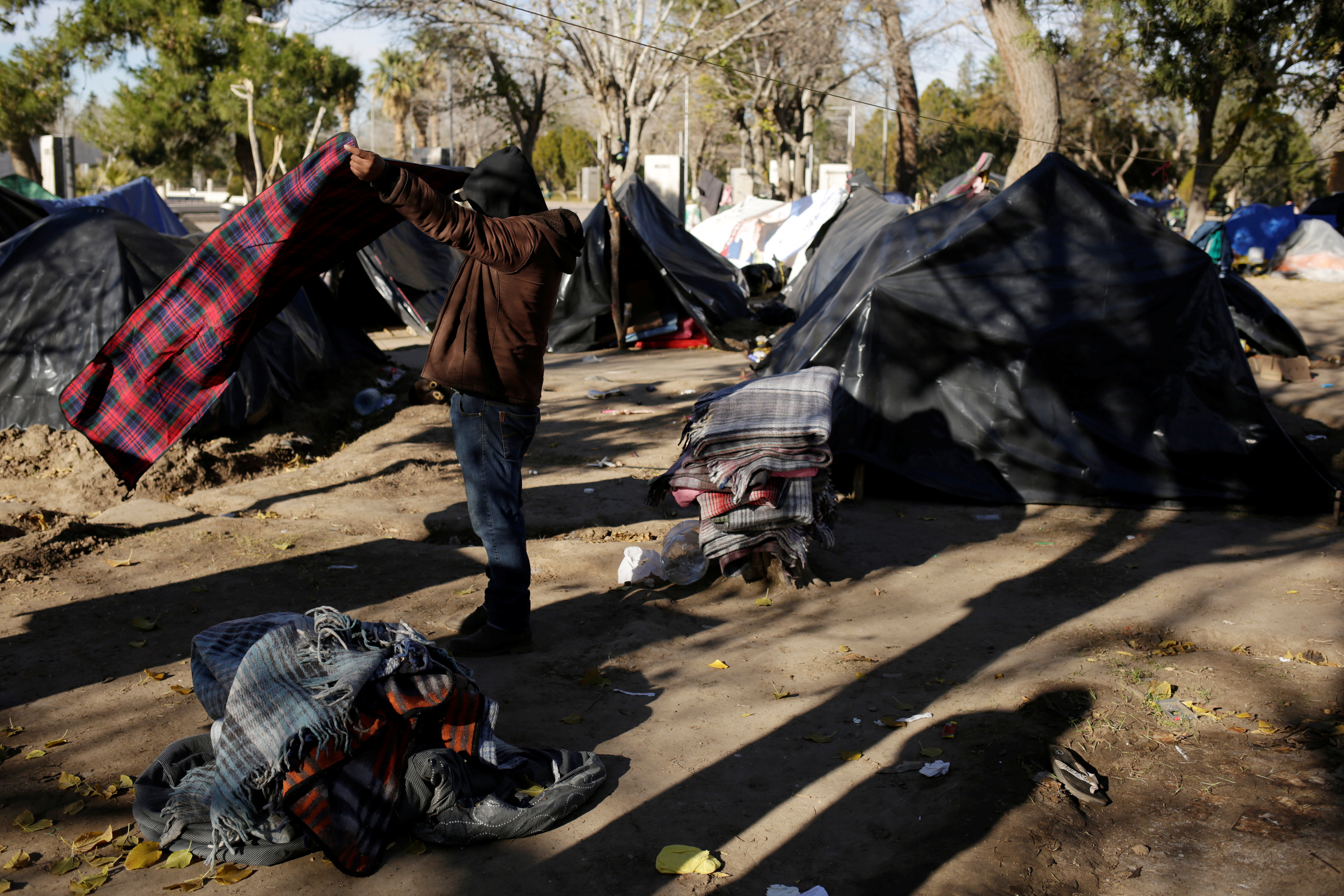 A Mexican man, who is fleeing from violence in his hometown and is currently camping near the Cordova-Americas international border crossing bridge while waiting to apply for asylum to the U.S., packs his belongings to move to a shelter as temperatures dropped below freezing in Ciudad Juarez, Mexico, December 18, 2019. REUTERS/Jose Luis Gonzalez