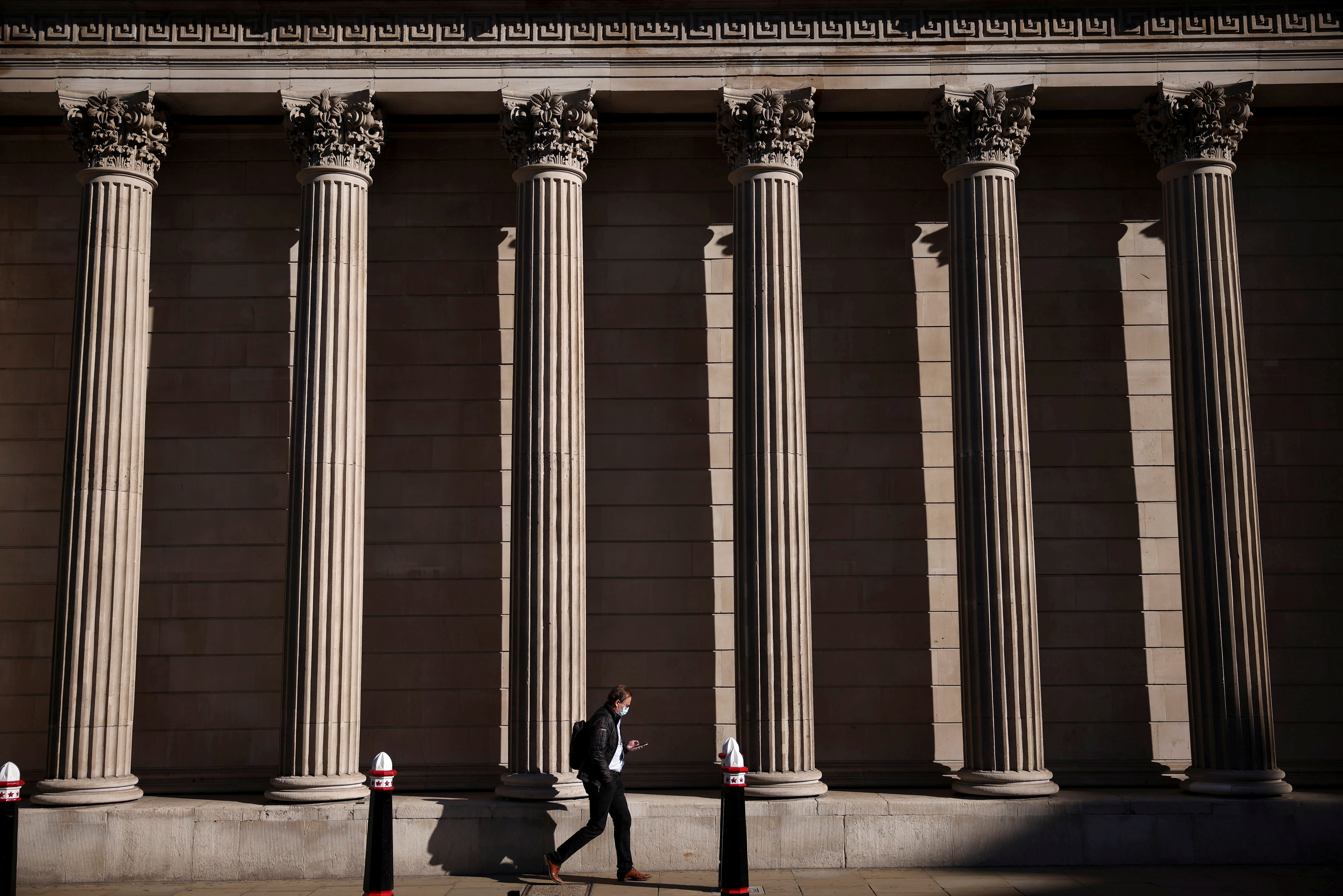 A person walks past the Bank of England during morning rush hour, amid the coronavirus disease (COVID-19) pandemic in London, Britain, July 29, 2021. REUTERS/Henry Nicholls/File Photo