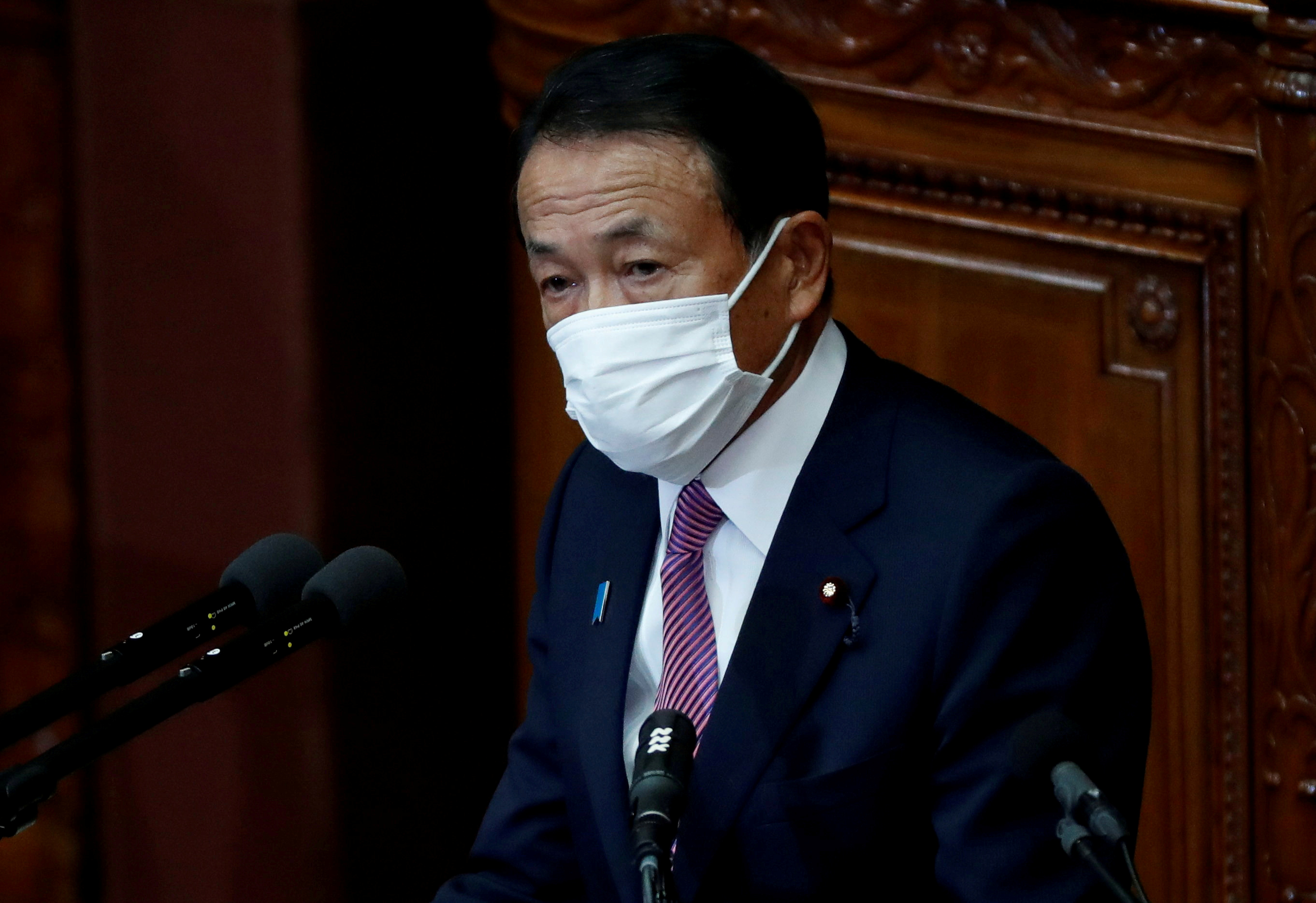 Japan's Deputy Prime Minister and Finance Minister Taro Aso, wearing a protective face mask, delivers his policy speech at the opening of an ordinary session of the parliament in Tokyo, Japan January 18, 2021. REUTERS/Issei Kato/File Photo