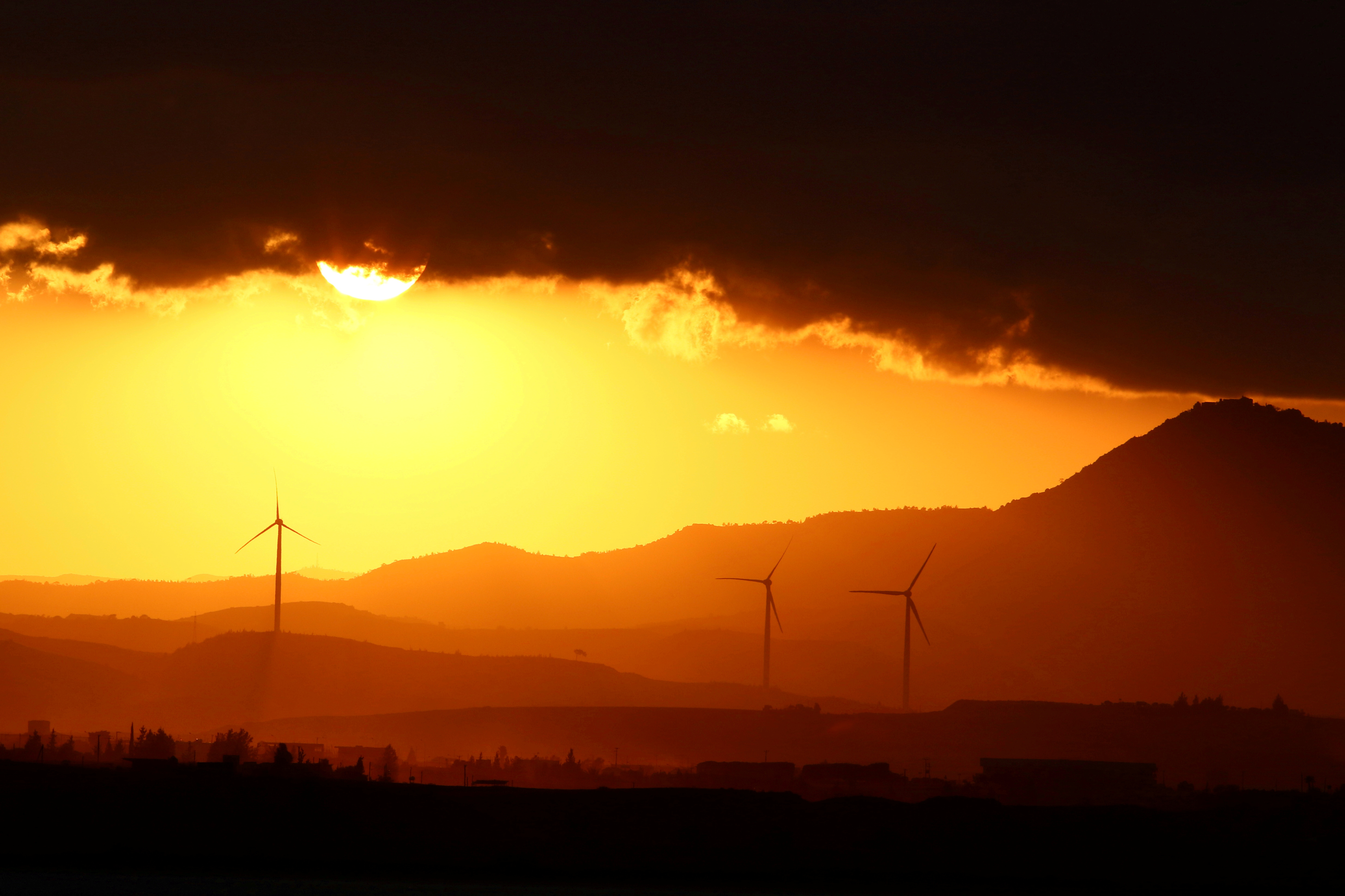 Power-generating windmill turbines are pictured during the sunset near Larnaca, Cyprus September 30, 2017. REUTERS/Yiannis Kourtoglou