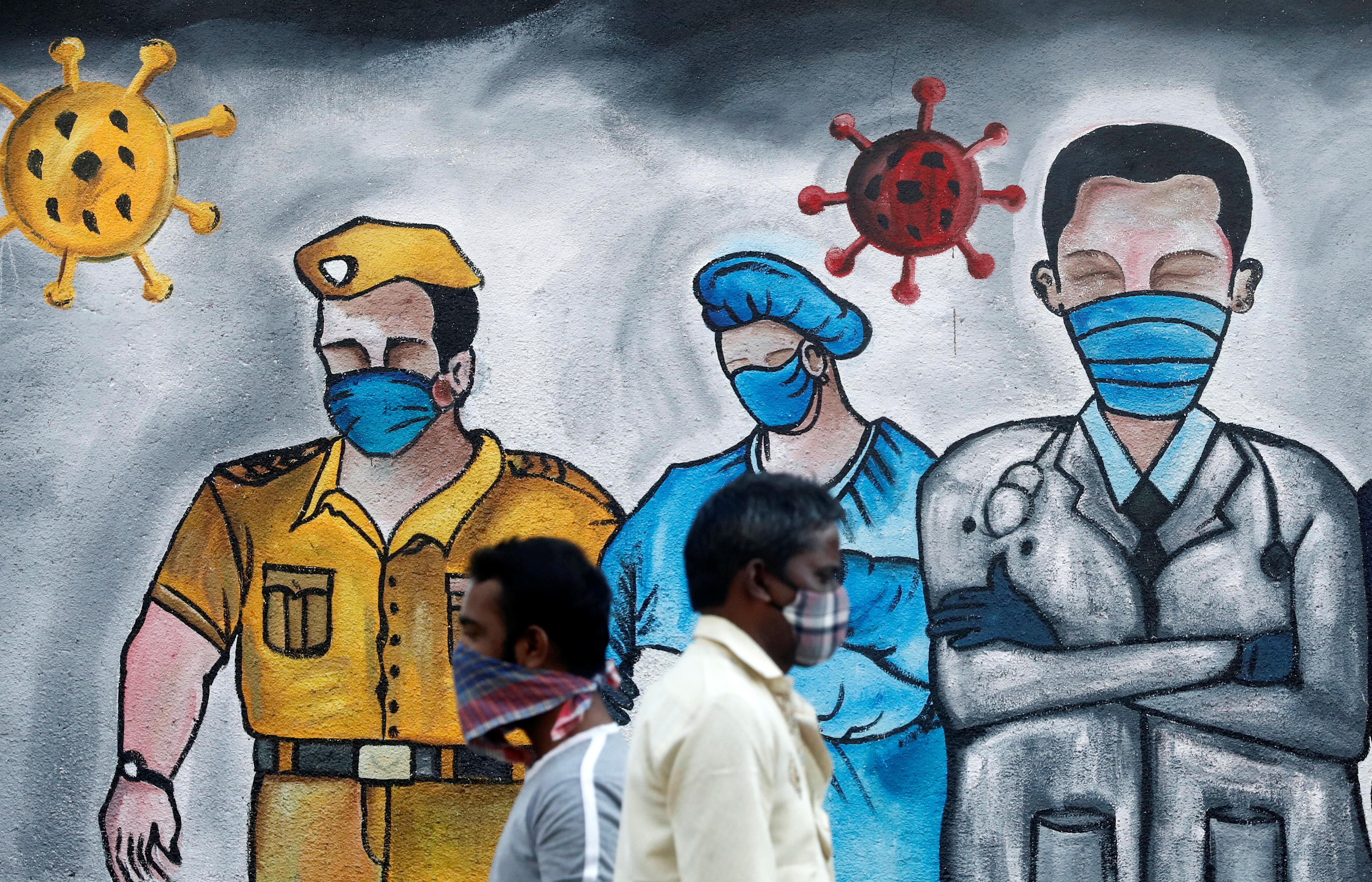 Men walk past a mural of frontline workers amid the spread of the coronavirus disease (COVID-19), in Mumbai, India, December 21, 2020. REUTERS/Francis Mascarenhas/Files