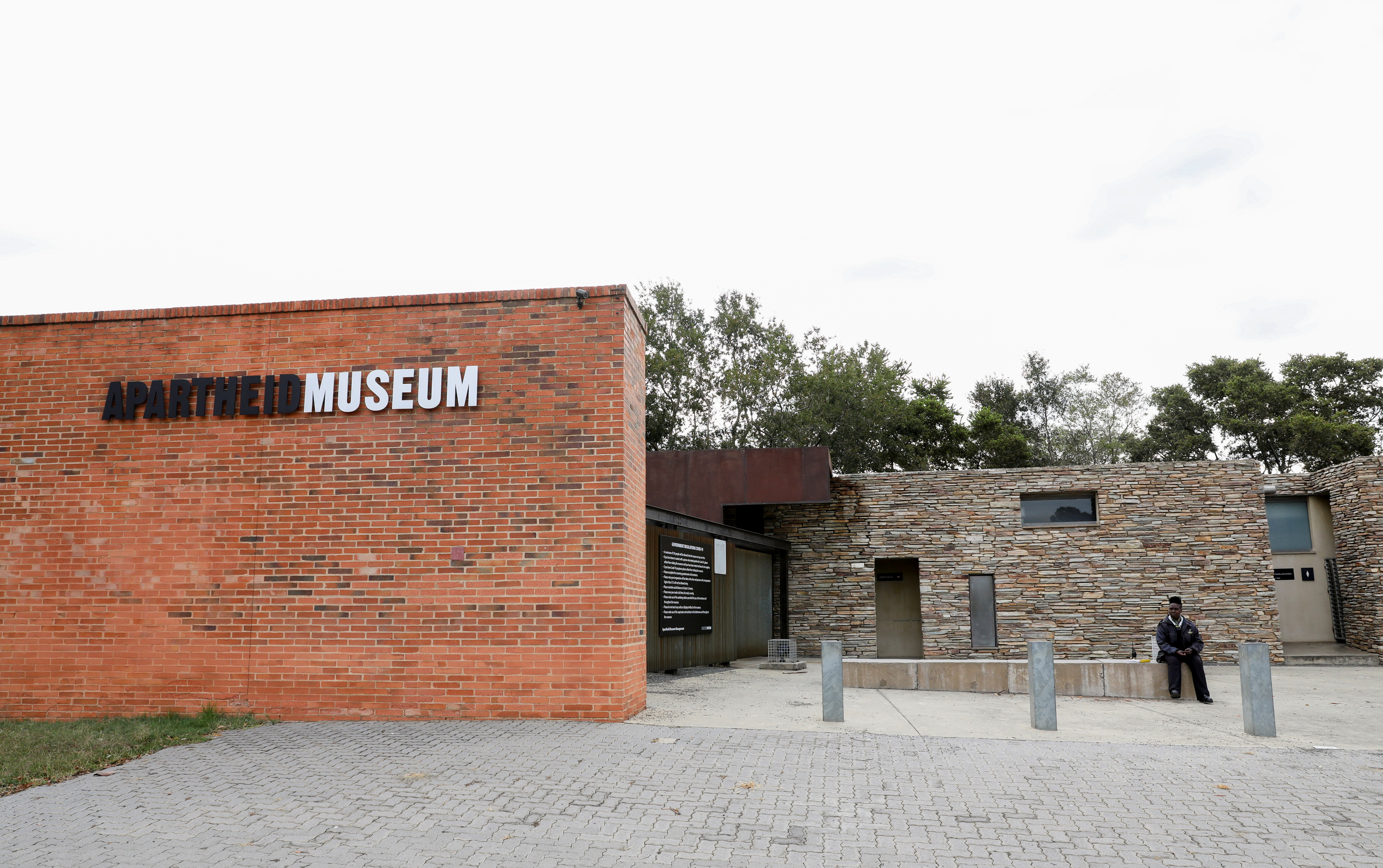 A security officer sits at the entrance of the Apartheid Museum, one of dozens of heritage attractions and art galleries around the country forced to close their doors due to the coronavirus disease (COVID-19) pandemic, in Johannesburg, South Africa April 7, 2021. REUTERS/Siphiwe Sibeko
