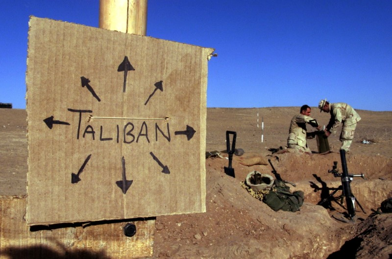 FILE PHOTO: U.S. Marines from Charlie 1/1 of the 15th MEU (Marine Expeditionary Unit) fill sandbags around their light mortar position on the frontlines of a U.S. Marine Corps base, near a cardboard sign reminding everyone that Taliban forces could be anywhere and everywhere, in southern Afghanistan December 1, 2001.  REUTERS/Jim Hollander/File Photo/File Photo