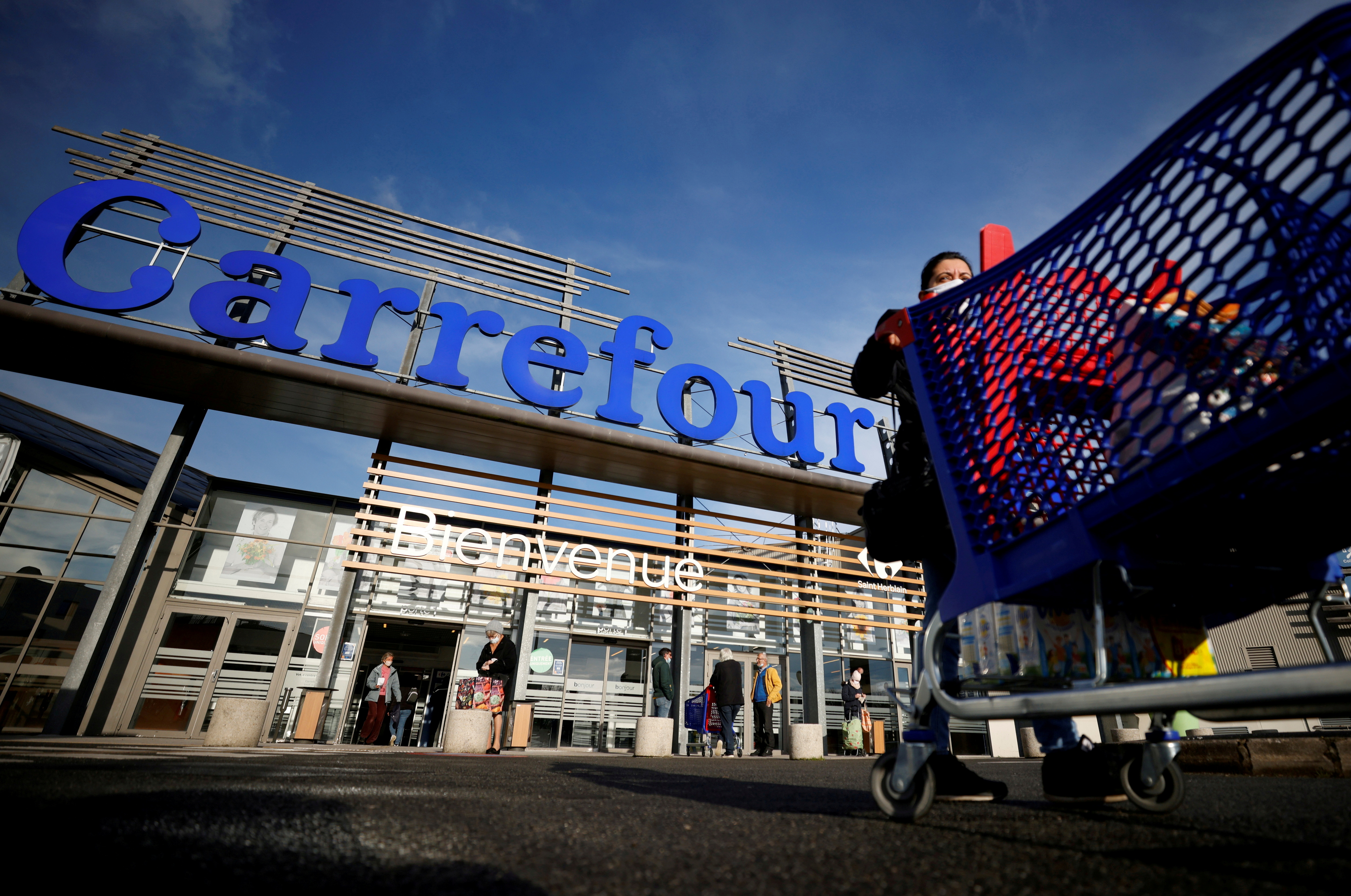 A customer pushes her shopping trolley in front of a Carrefour Hypermarket store in Saint-Herblain near Nantes, France January 15, 2021. REUTERS/Stephane Mahe/File Photo