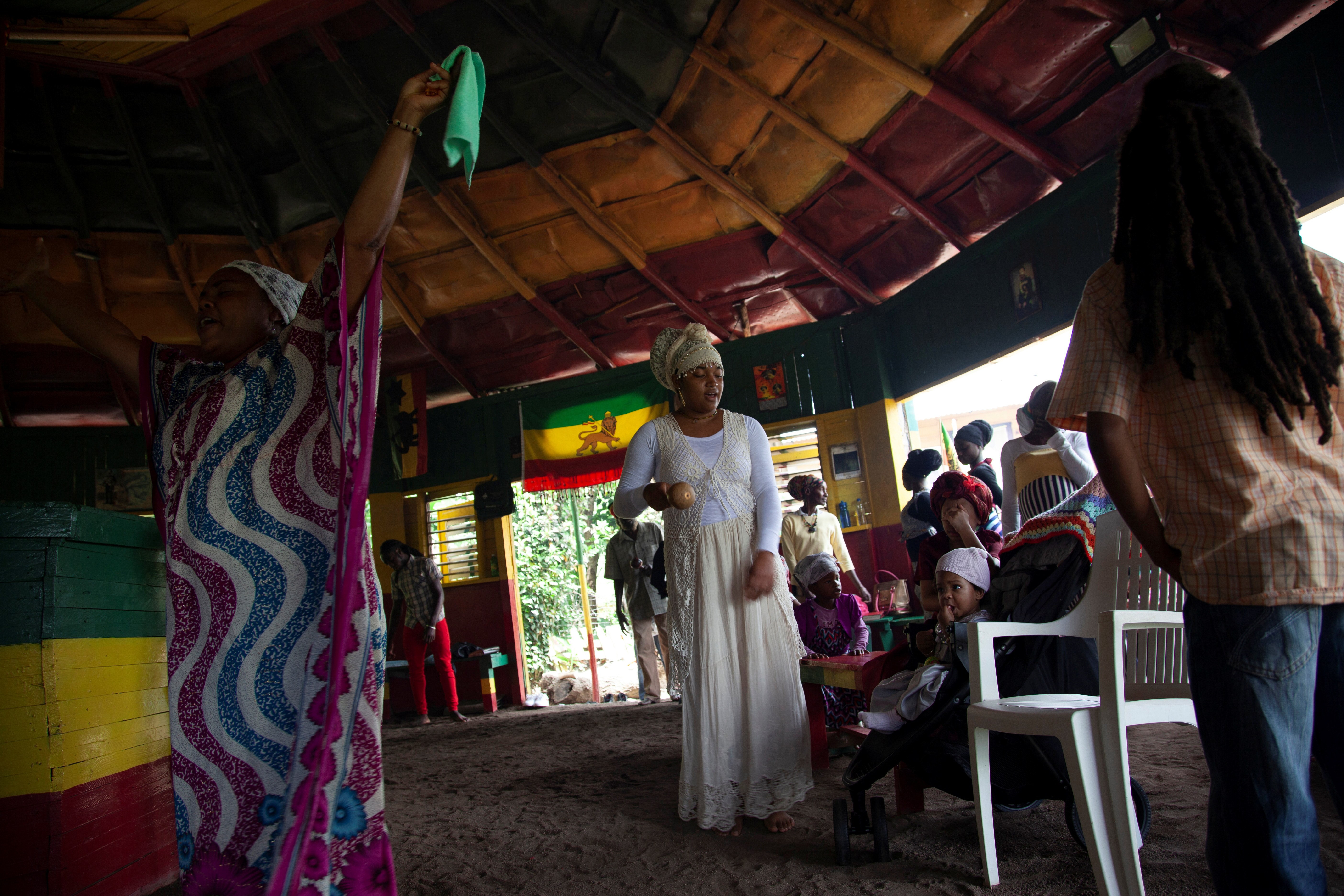 Treesha Bailey (L) and Tasheia Williams chant and dance to celebrate the Sabbath in a ceremony known as nyabinghi, at the temple of The School of Vision, a Rastafari farming community in the Blue Mountains, near Kingston, Jamaica, on June 19, 2021.   REUTERS/Ina Sotirova