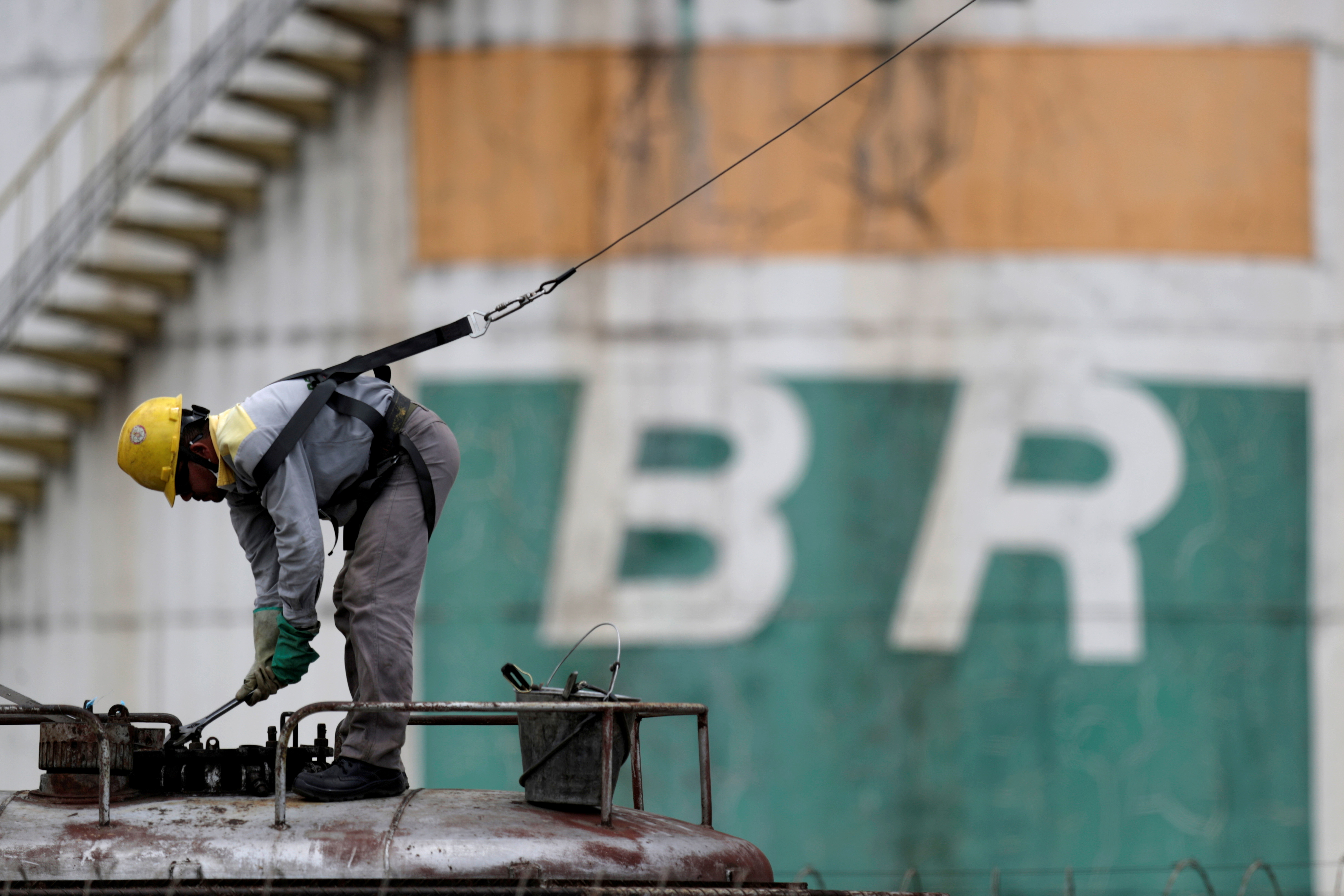 A worker checks the fuel volumes on a train wagon near a tank of Brazil's state-run Petrobras oil company in Brasilia, Brazil, February 19, 2021. REUTERS/Ueslei Marcelino/File Photo