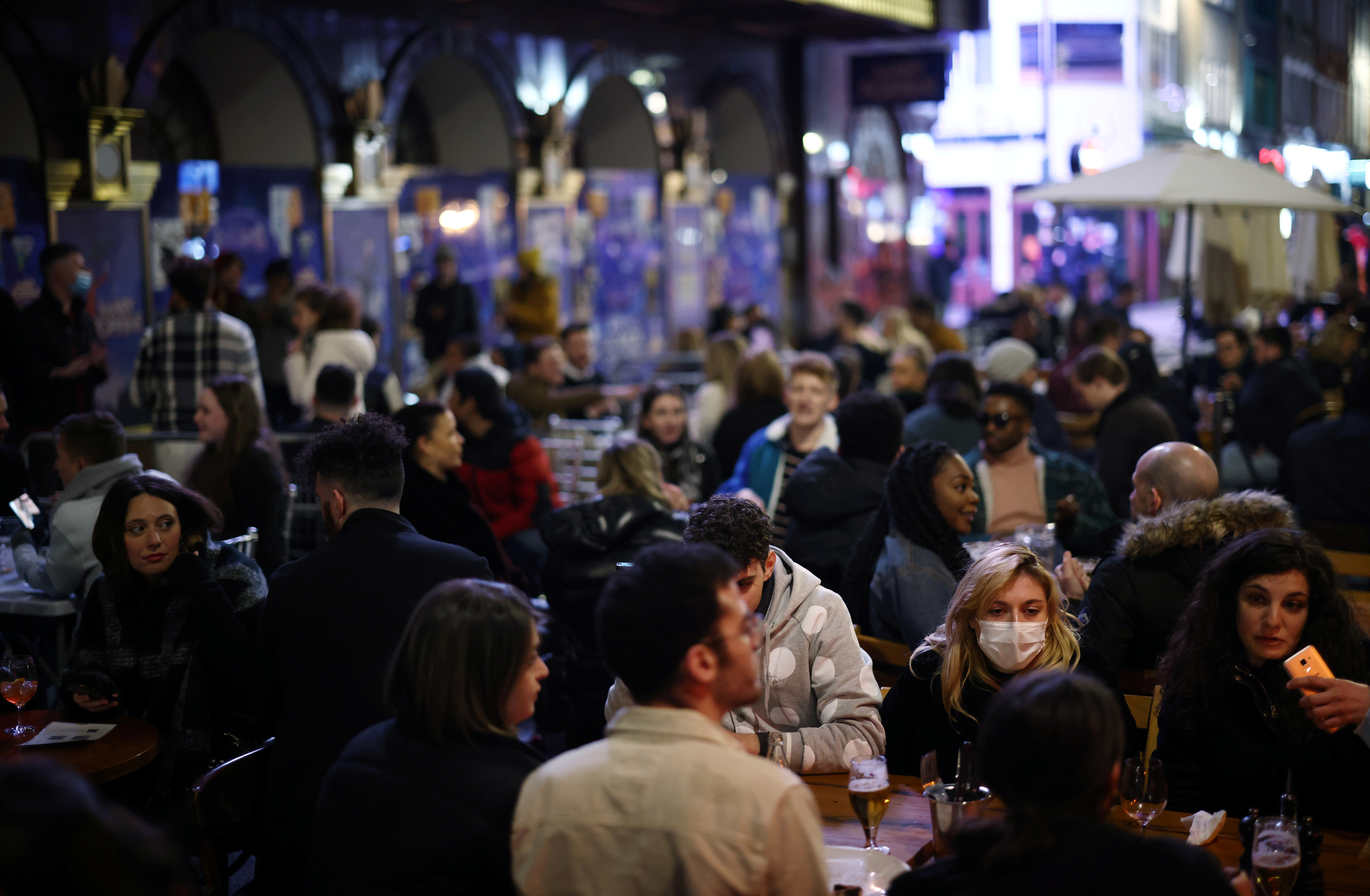 People enjoy the evening at an outside restaurant area in Soho, as the coronavirus disease (COVID-19) restrictions ease, in London, Britain April 12, 2021. REUTERS/Henry Nicholls/File photo