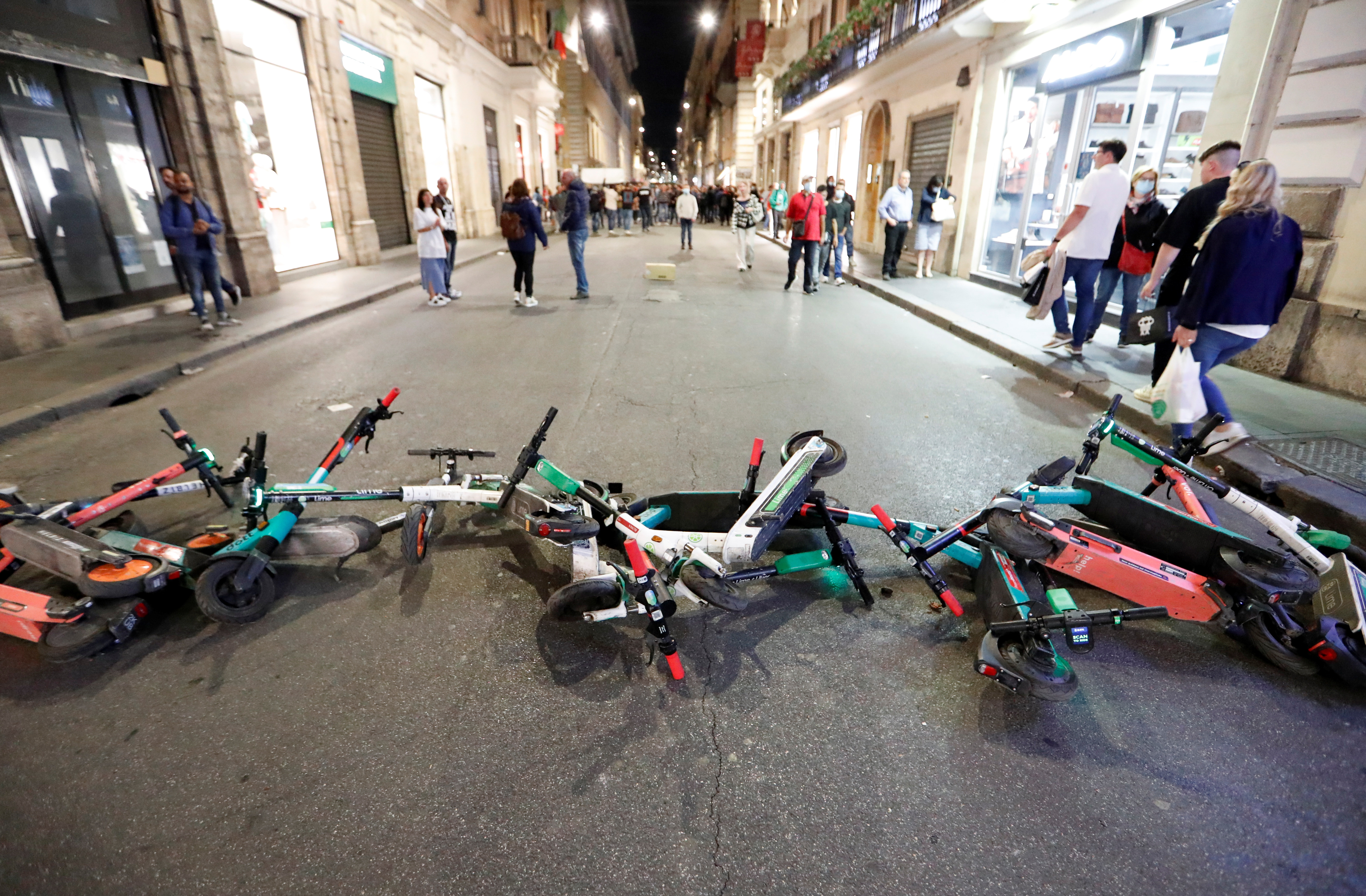 Scooters are laid down on Via del Corso street during a protest against the government's introduction of the