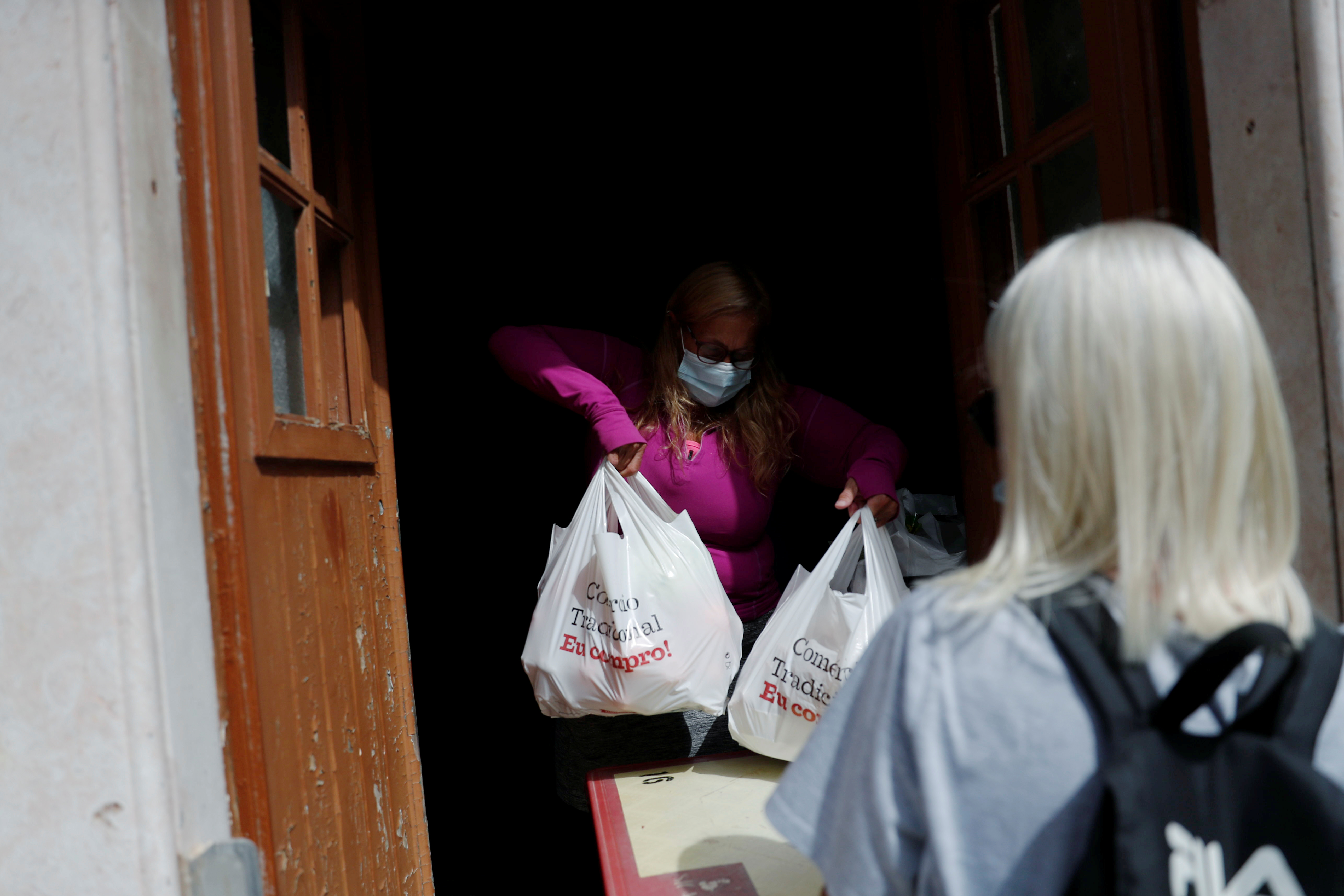 Volunteers work at East Algarve Families in Need Food Bank, during the coronavirus disease (COVID-19) pandemic in Tavira, Portugal, March 31, 2021. Picture taken March 31, 2021. REUTERS/Pedro Nunes