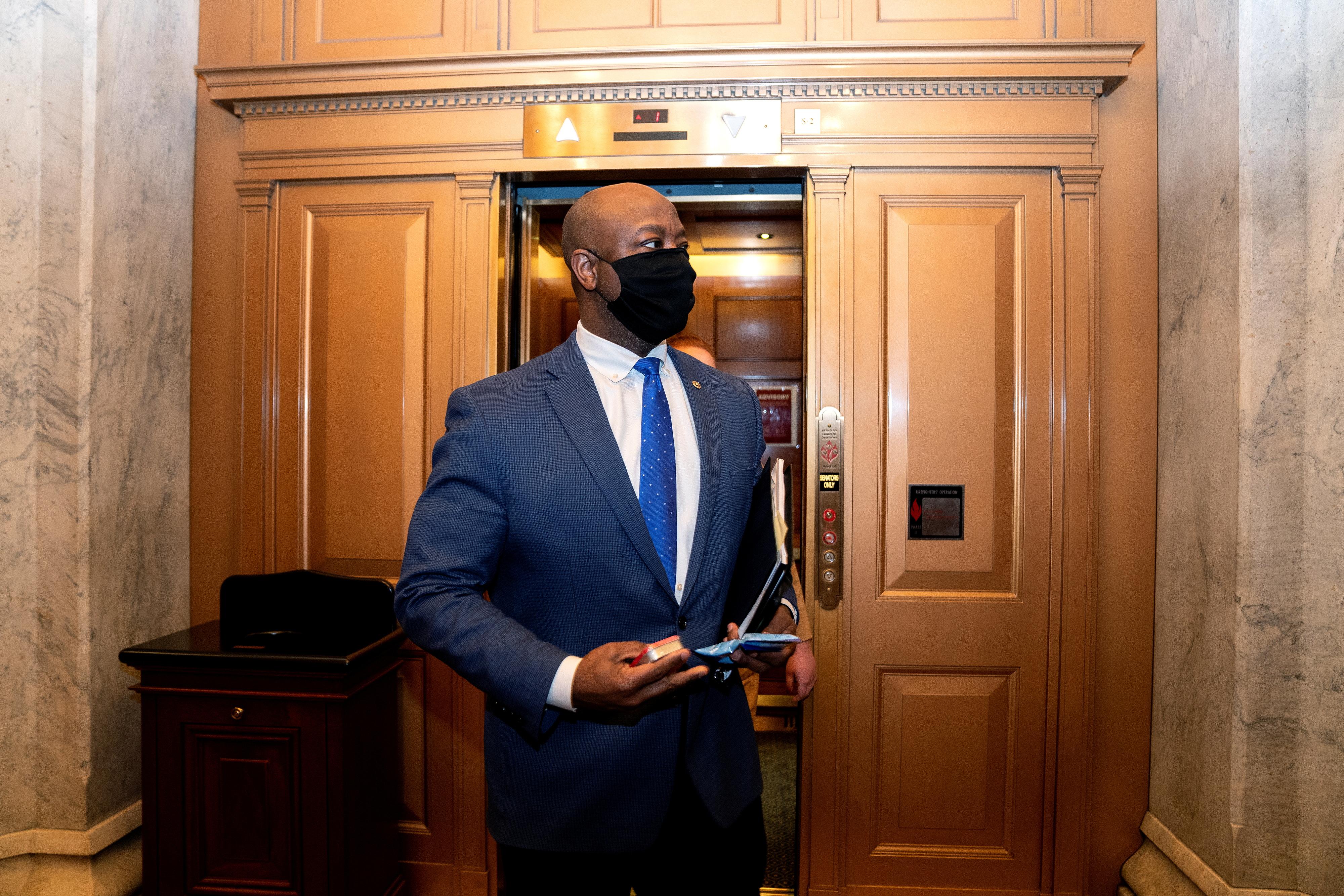 U.S. Senator Tim Scott (R-SC) wears a protective mask while departing the U.S. Capitol in Washington, U.S., February 13, 2021. Stefani Reynolds/Pool via REUTERS