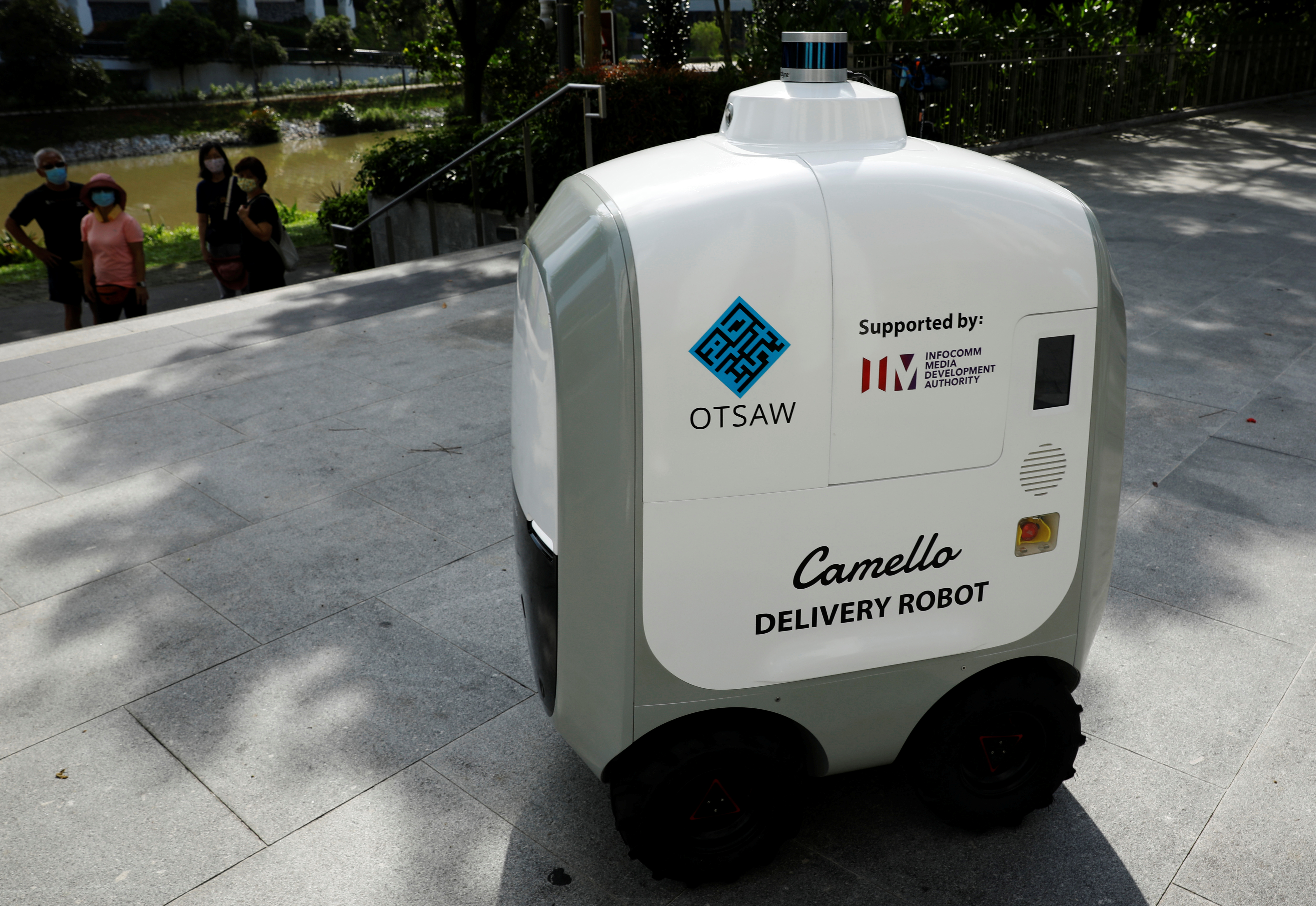 People look on as Camello, an autonomous grocery delivery robot, makes its way during a delivery in Singapore April 6, 2021. REUTERS/Edgar Su