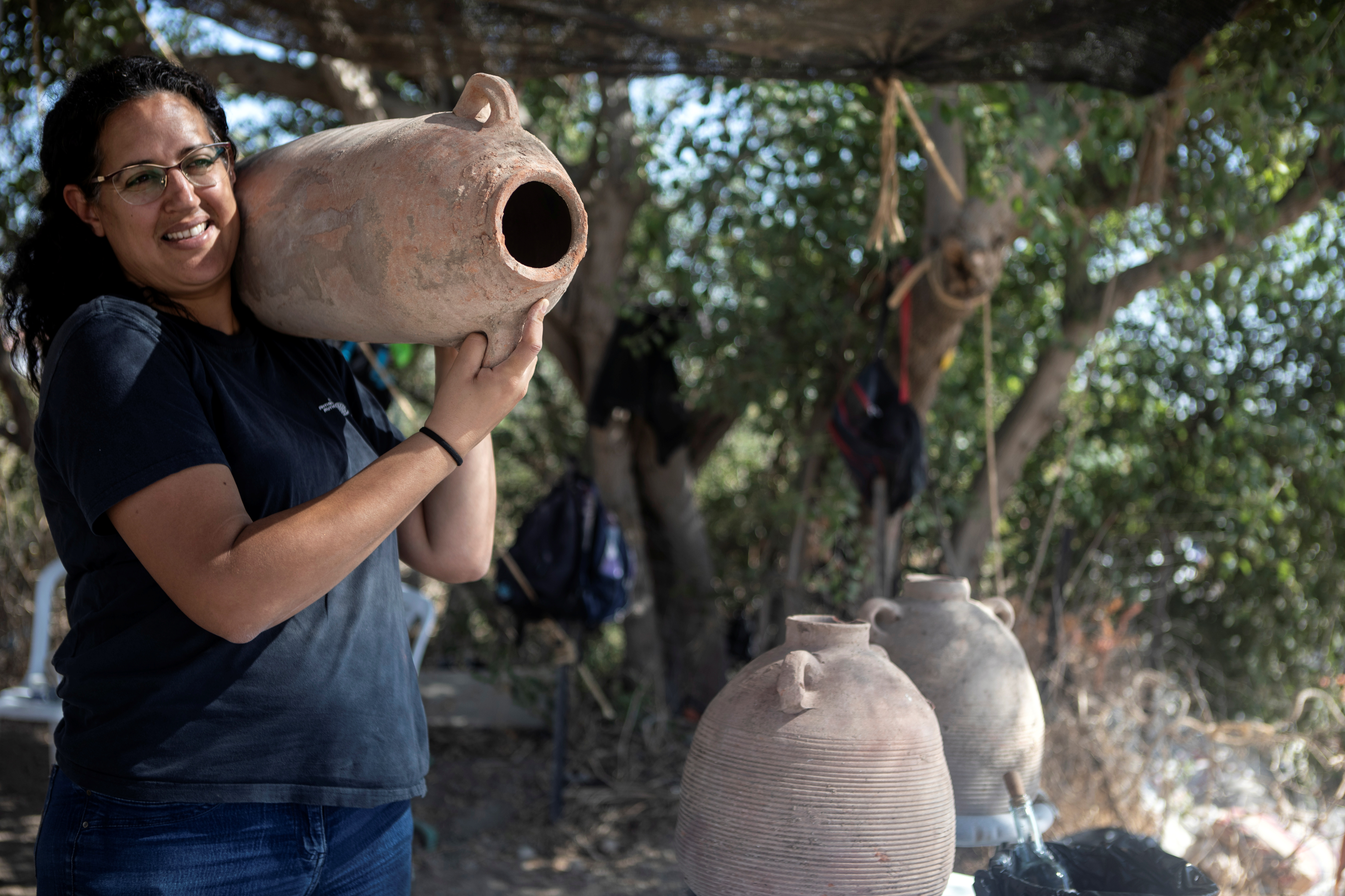 Liat Nadav-Ziv, one of the directors of the excavation of a 1500-year-old Byzantine winery on behalf of the Israel Antiquities Authority, carries a Gaza Jar in Yavne, Israel October 11, 2021. REUTERS/Nir Elias