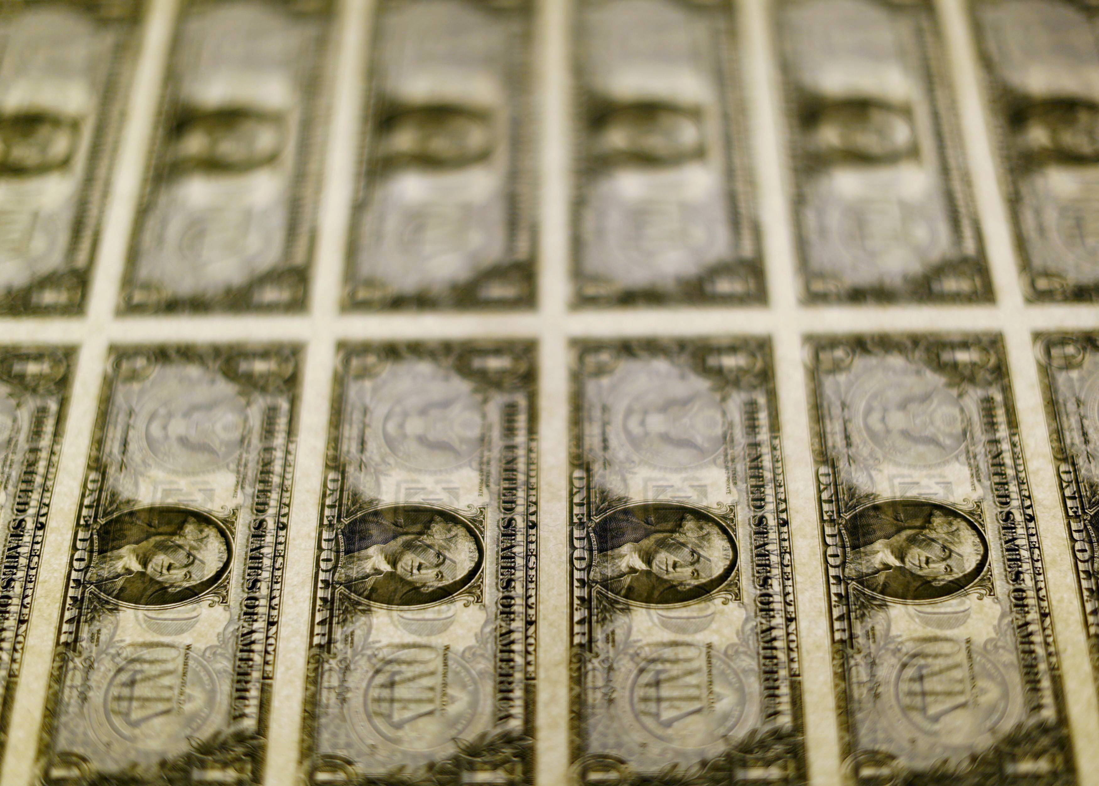 United States one dollar bills are seen on a light table at the Bureau of Engraving and Printing in Washington November 14, 2014. REUTERS/Gary Cameron