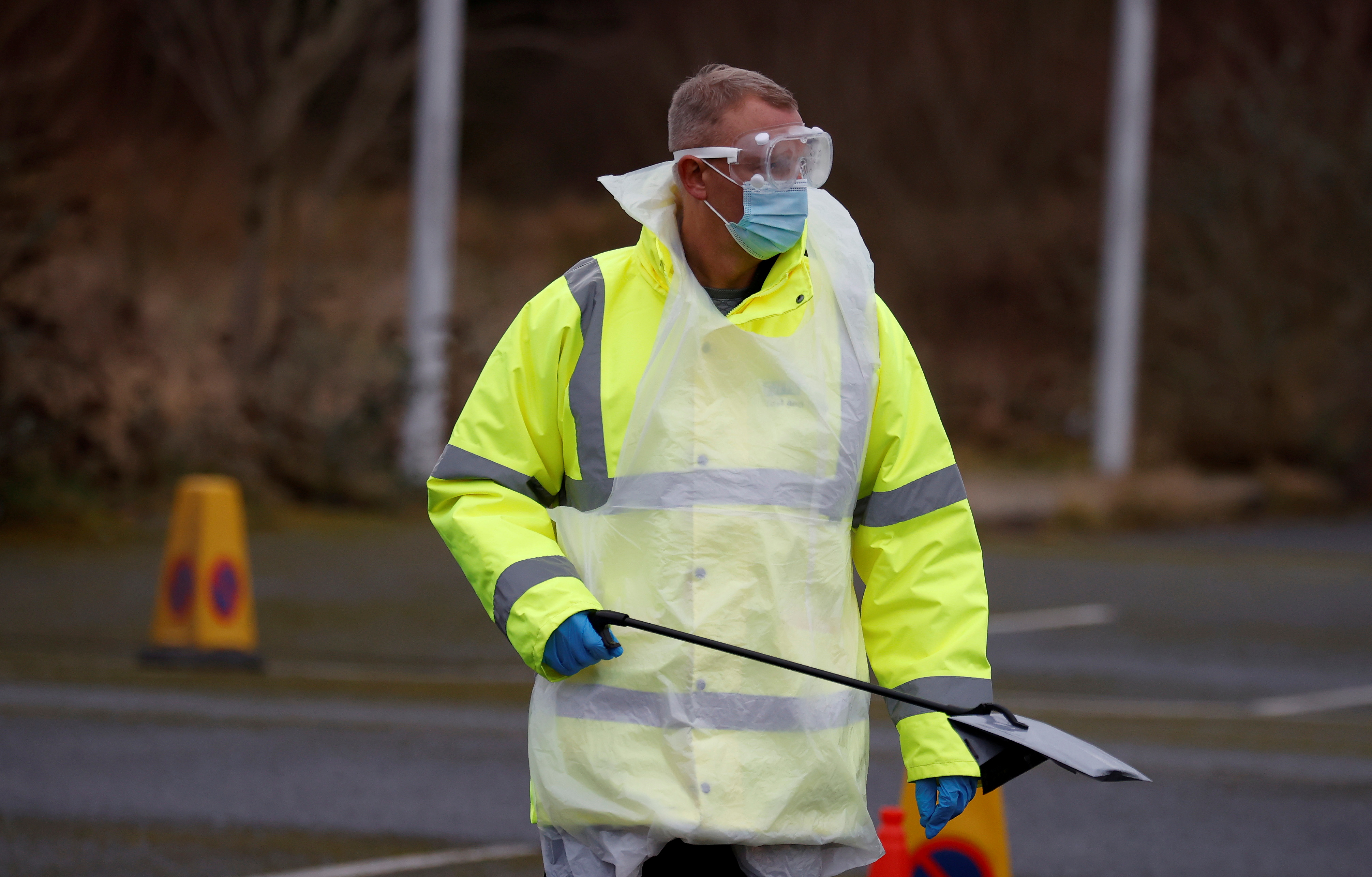 A member of NHS Test and Trace staff carries a testing kit as they arrive at a mobile testing centre amid the outbreak of the coronavirus disease (COVID-19) in Southport, Britain, February 3, 2021. REUTERS/Phil Noble