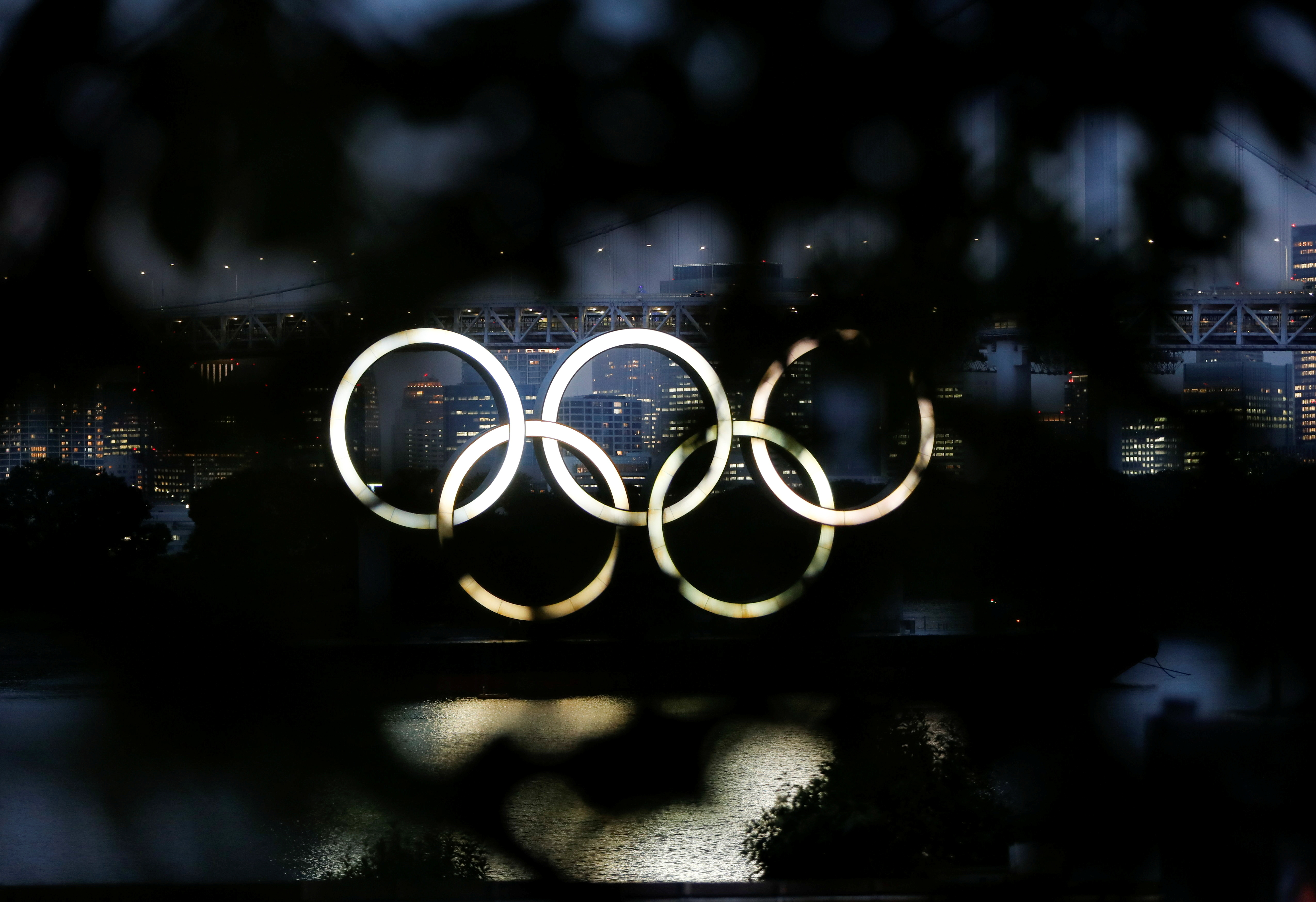 The giant Olympic rings are seen through a tree in the dusk at the waterfront area of Odaiba Marine Park, before the opening ceremony of the 2020 Tokyo Olympic Games that have been postponed to 2021 due to the coronavirus disease (COVID-19) outbreak, in Tokyo, Japan July 8, 2021.  REUTERS/Issei Kato