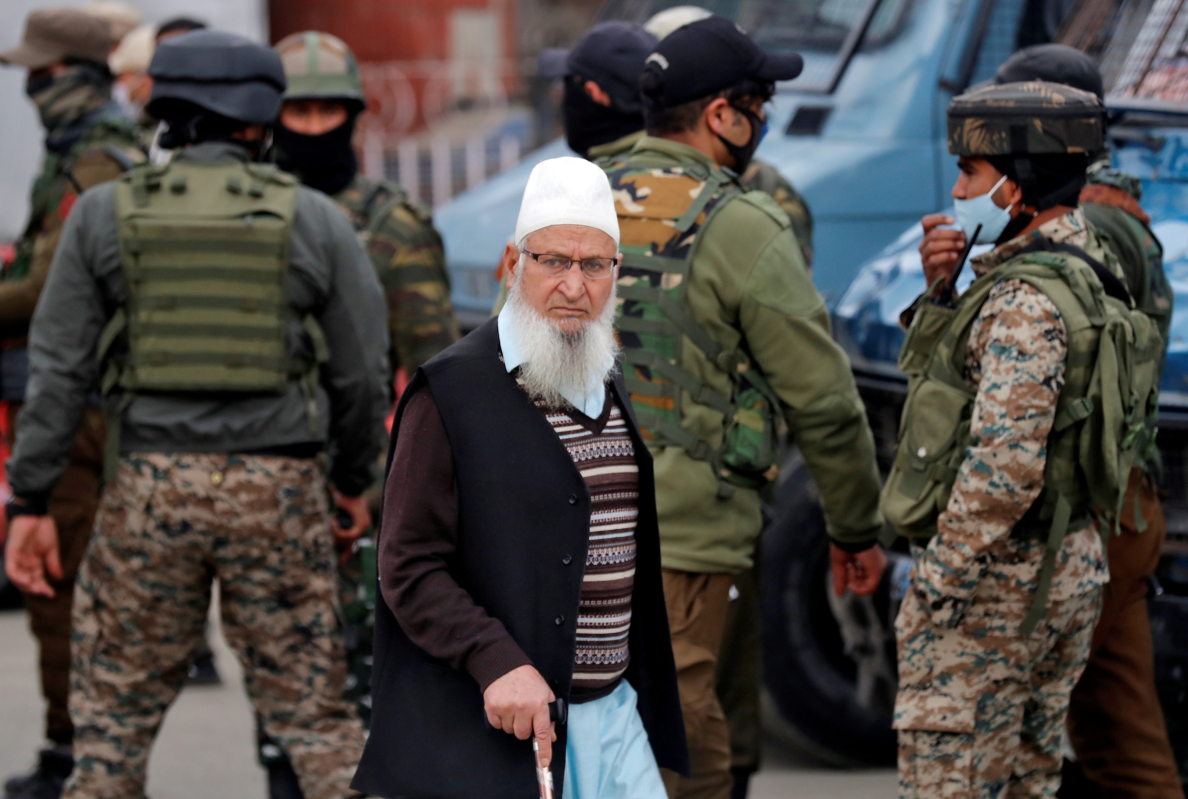 A Kashmiri Muslim man walks past Indian security force personnel standing guard during a cordon and search operation, in Srinagar February 26, 2021. REUTERS/Danish Ismail/File Photo