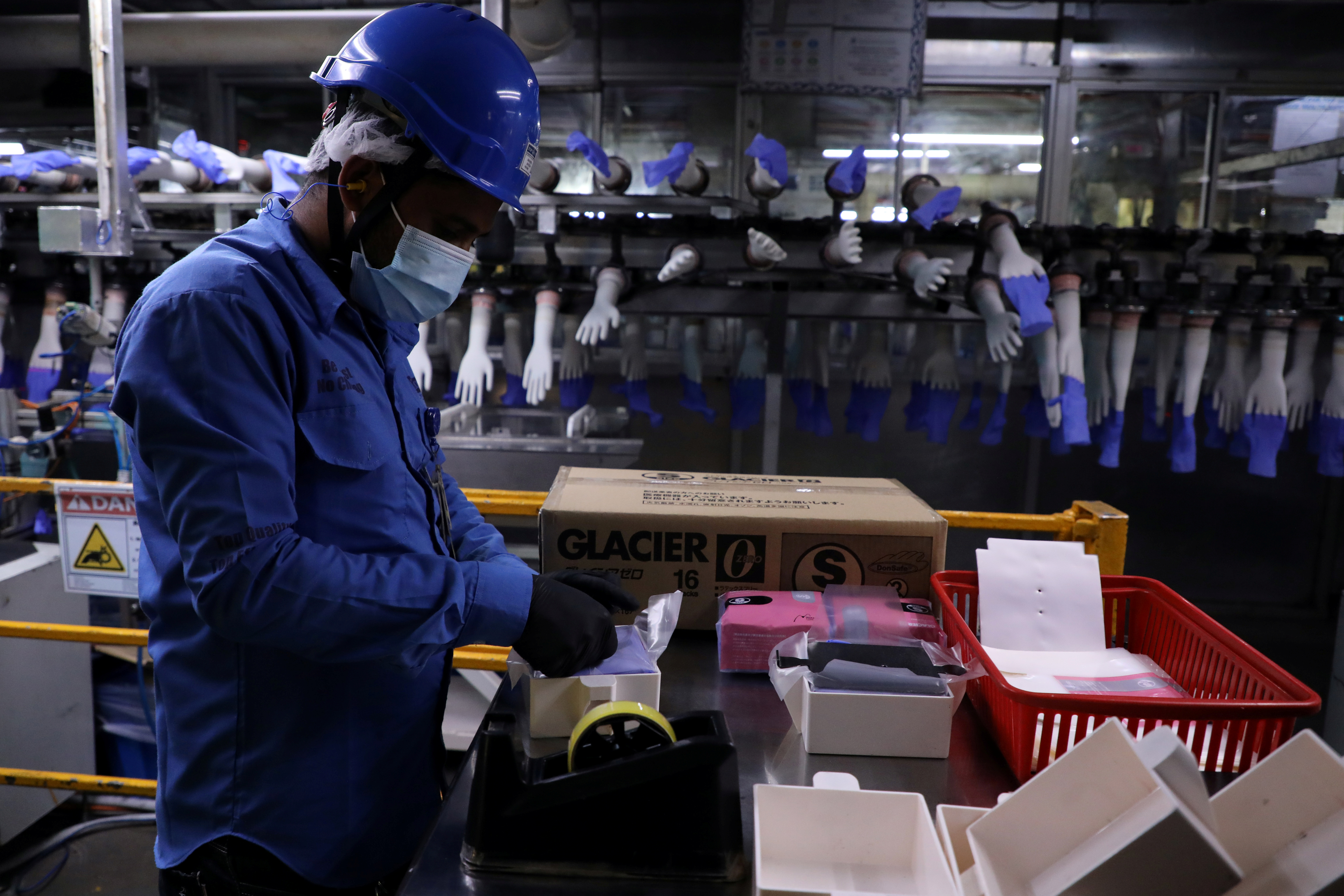 A worker works at a production line in Top Glove factory in Shah Alam, Malaysia August 26, 2020. REUTERS/Lim Huey Teng