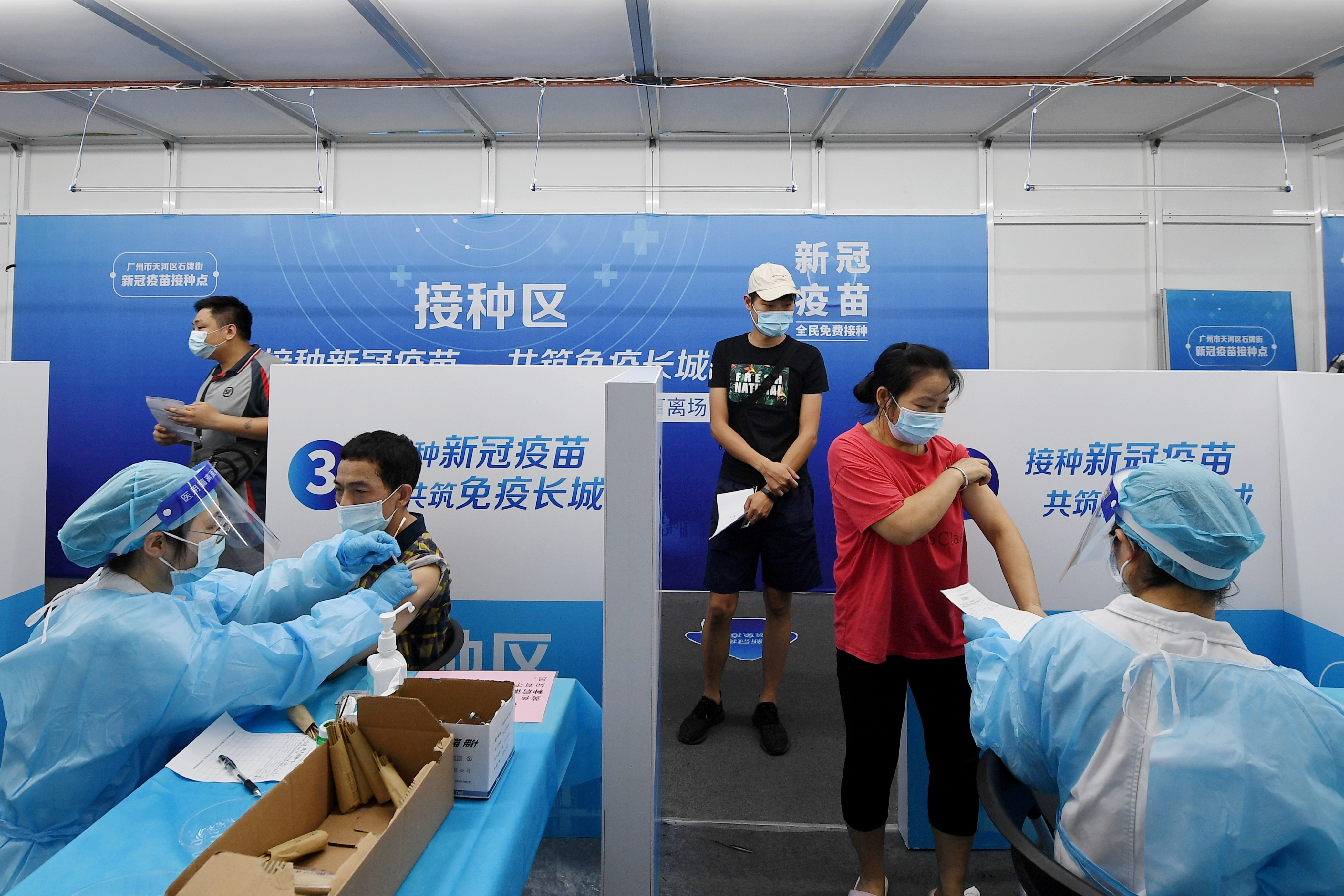 Residents receive vaccines against the coronavirus disease (COVID-19) at a makeshift vaccination site in Guangzhou, Guangdong province, China June 21, 2021. Picture taken June 21, 2021. cnsphoto via REUTERS