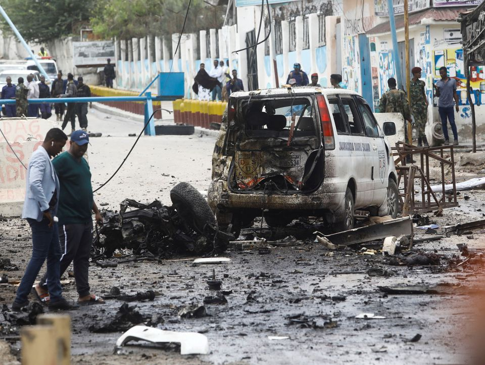 Civilians and Somalian security officers gather at the scene of a suicide car bomb at a street junction near the president's residence, in Mogadishu, Somalia. REUTERS/Feisal Omar
