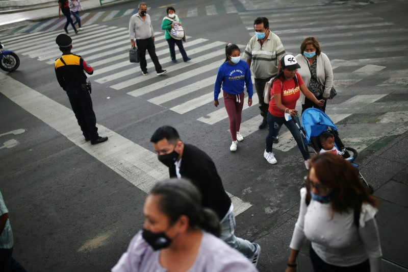 People wearing face masks walk along a street as Mexico City's authorities announce a full reopening of the city come Monday, the first time since the coronavirus disease (COVID-19) pandemic, Mexico June 4, 2021. REUTERS/Edgard Garrido
