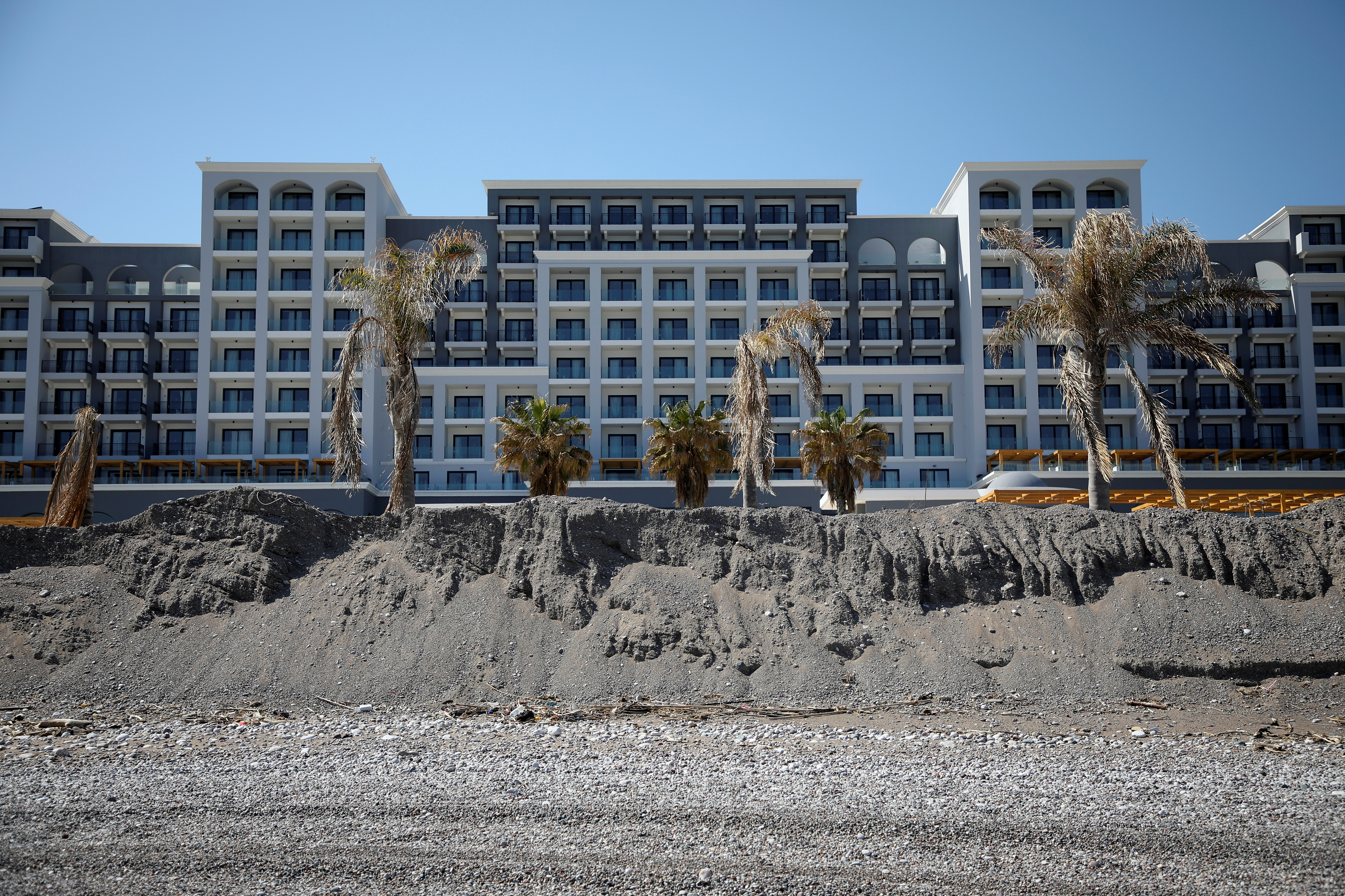 Sand hills are formed in front of a hotel, in order to be spread on the beach at the beginning of the tourist season, at Ammoudes Beach, amid the coronavirus disease (COVID-19) pandemic, on the island of Rhodes, Greece, April 12, 2021.  REUTERS/Louiza Vradi