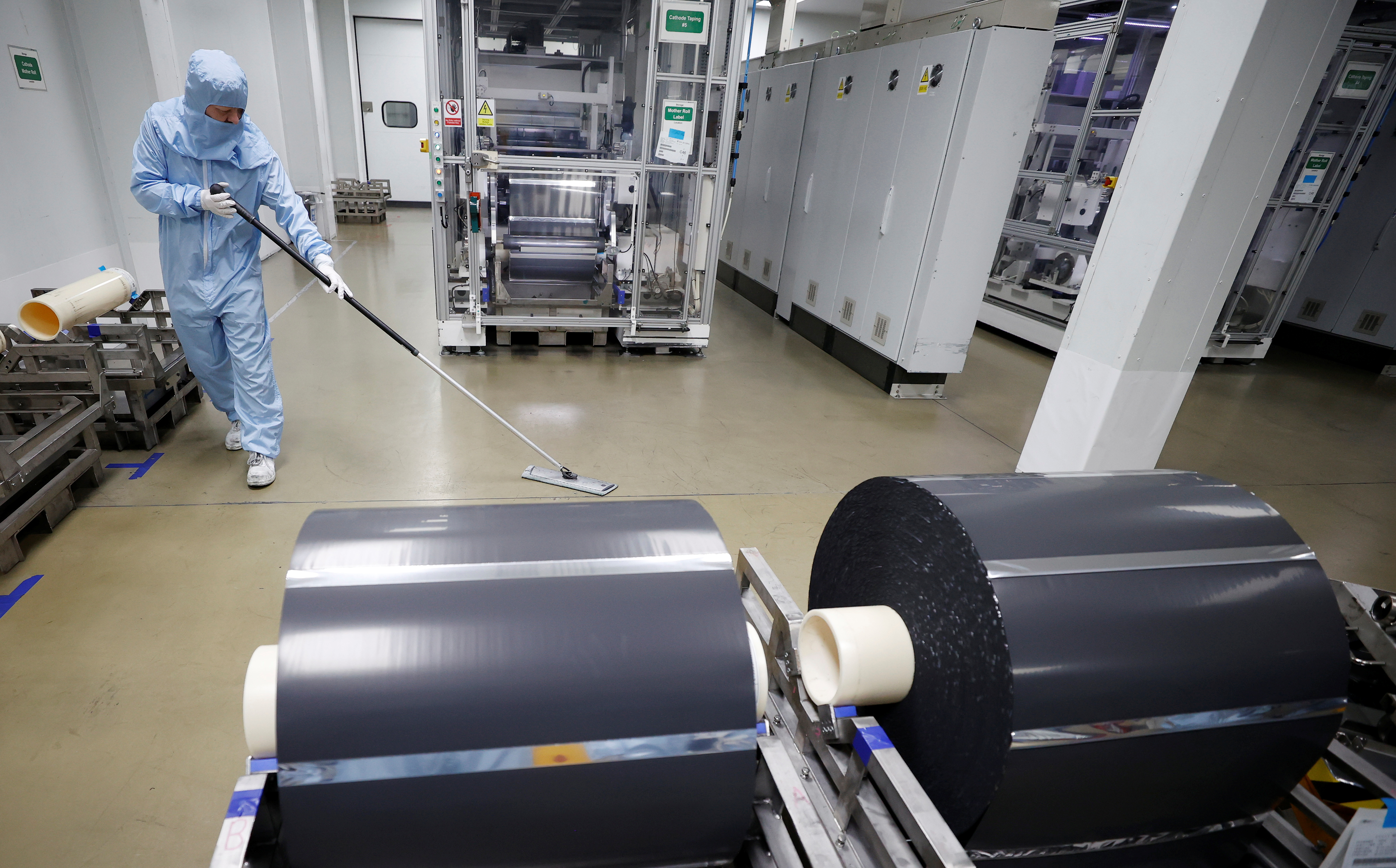 A worker in a protective suit sweeps the floor inside the Envision battery manufacturing plant at Nissan's Sunderland factory, Britain, July 1, 2021. REUTERS/Phil Noble