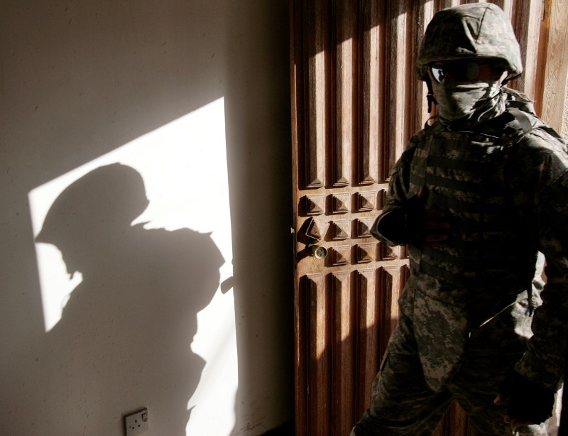 An Iraqi interpreter enters a house during a patrol with U.S. army Alpha Company 1-64 Armored in the neighborhood of Adl in Baghdad November 7, 2007. REUTERS/Stefano Rellandini/File Photo