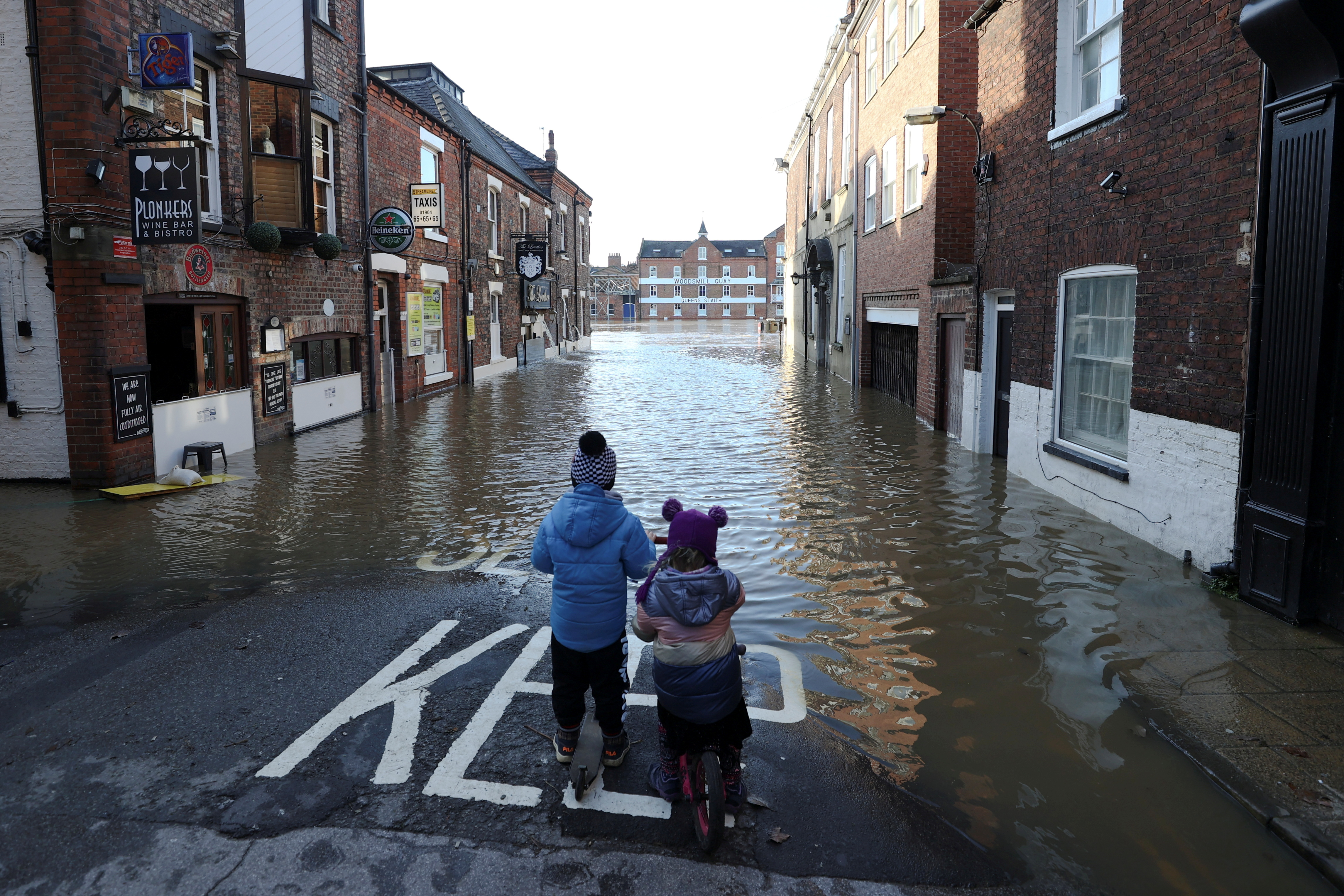 Two children stand on a partially flooded street after the River Ouse burst banks in York, Britain, January 22, 2021. REUTERS/Lee Smith