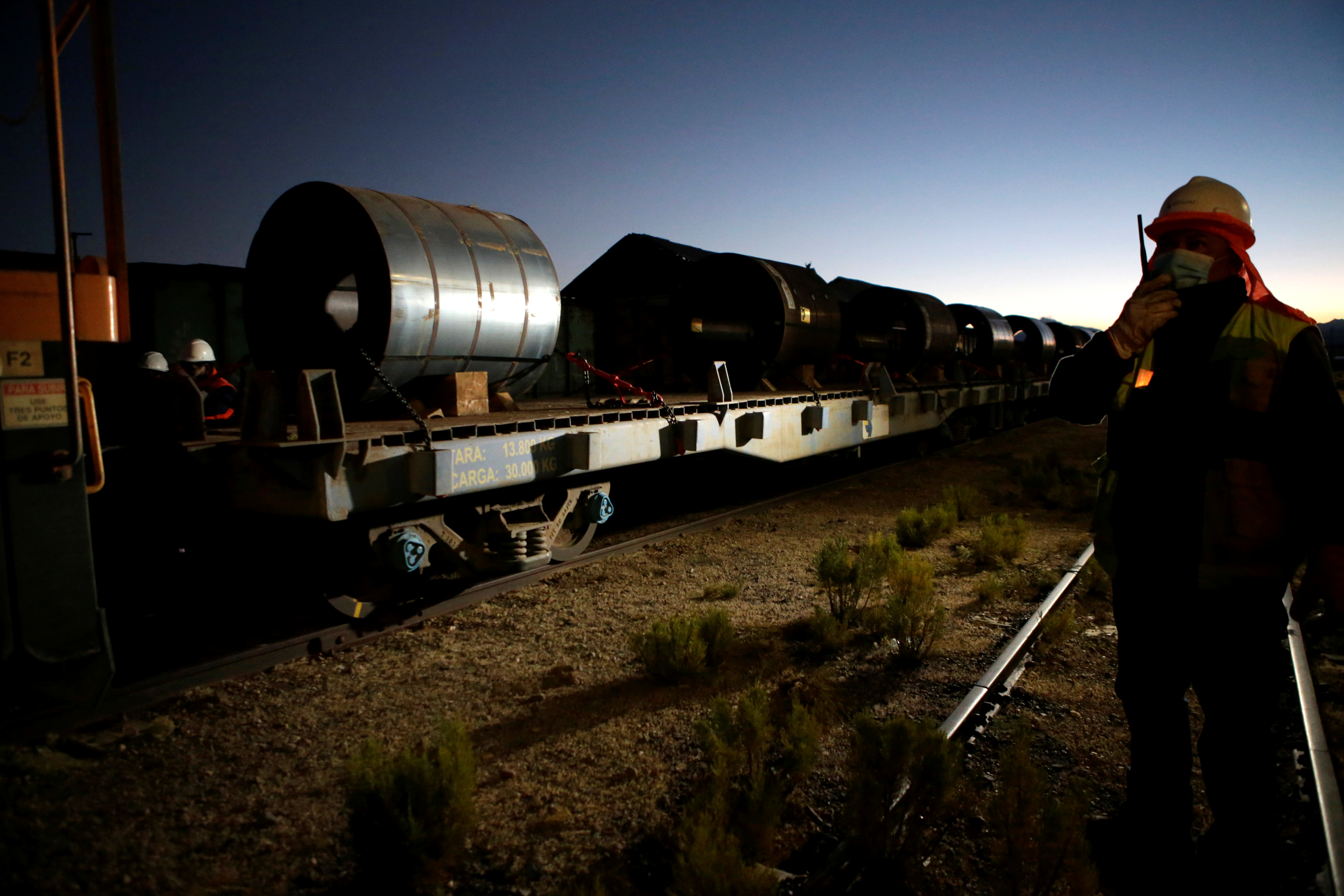 A railway worker stands next to a cargo of iron coil brought by Chile's Arica-La Paz Railway and to be taken to Bolivia, at the border between Chile and Bolivia, in Visviri, Chile May 7, 2021. Picture taken May 7, 2021. REUTERS/Manuel Claure
